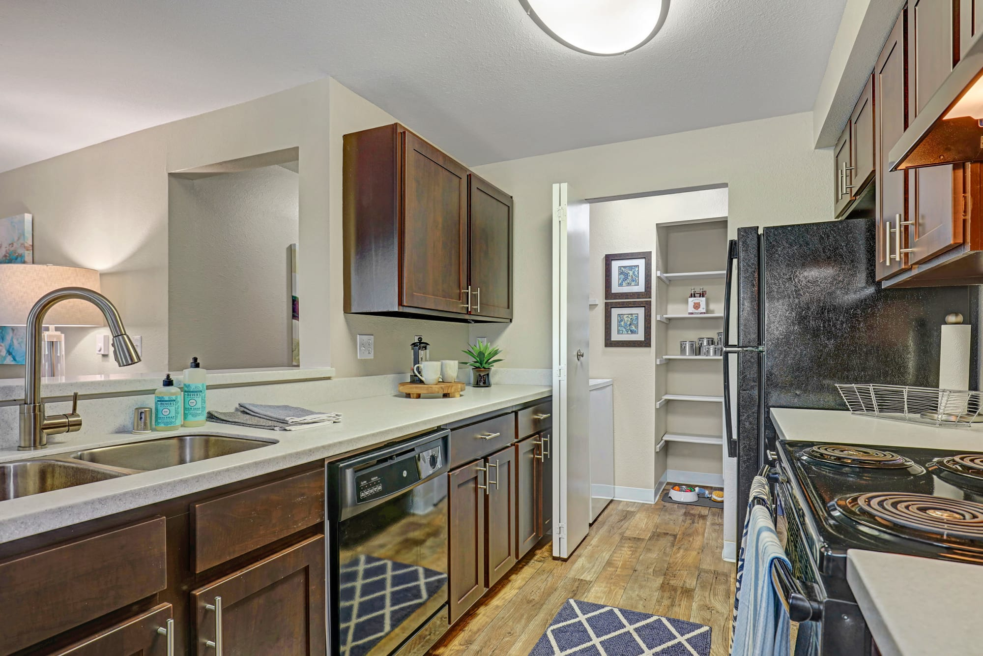 A kitchen with dark wood cabinets, black appliances and hardwood floors at Cascade Ridge in Silverdale, Washington