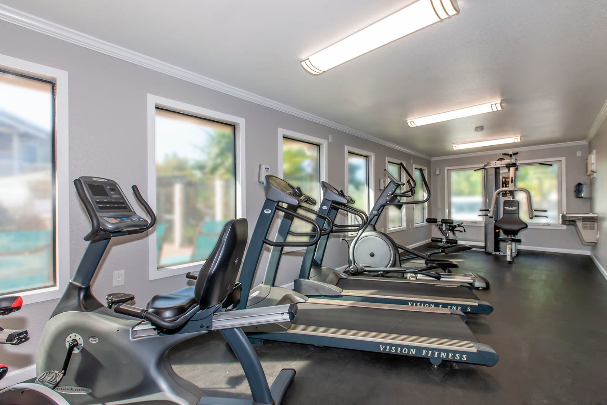 Fitness Center with cardio machines looking through large windows out to the pool area at Sommerset Apartments in Vacaville, CA