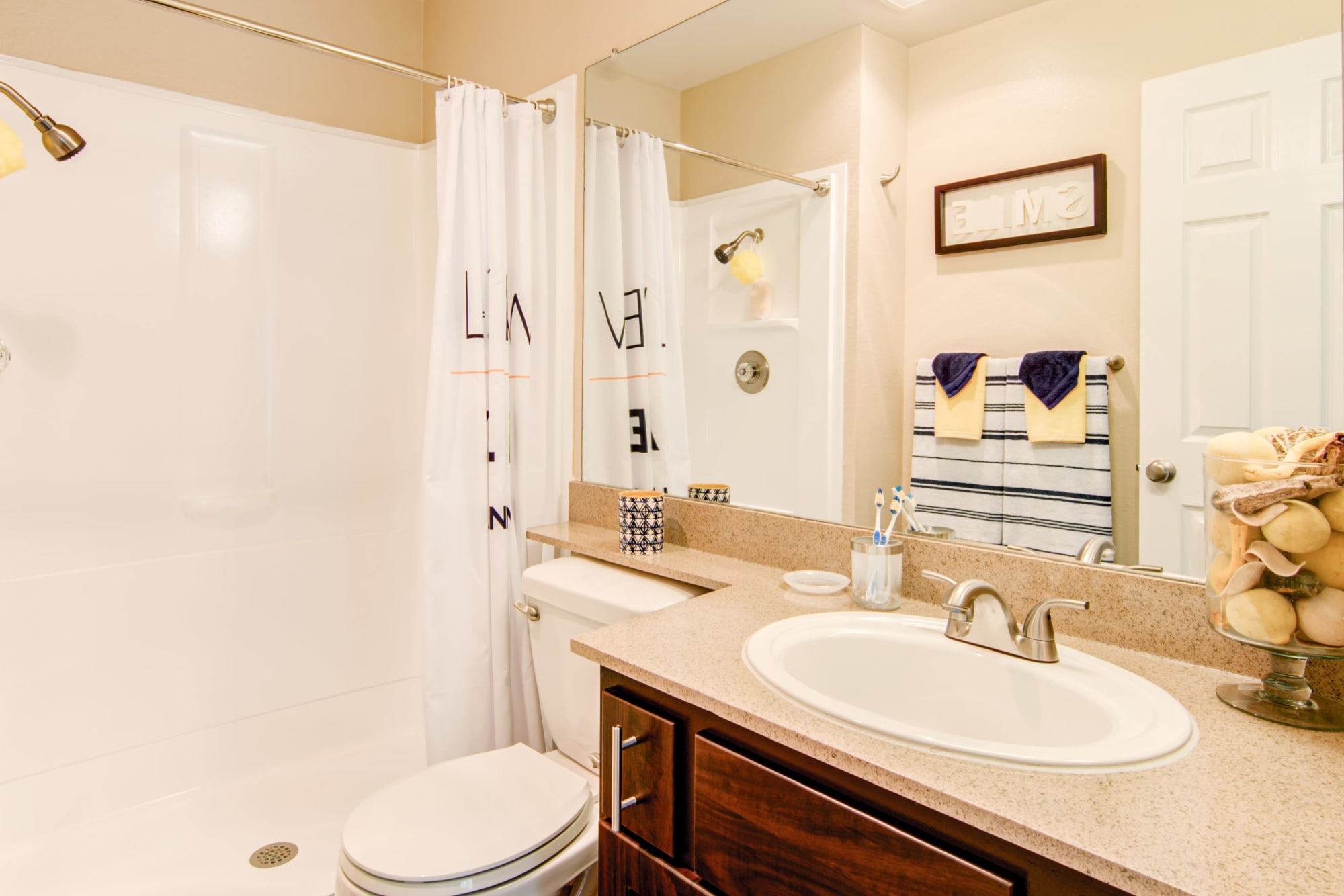 A renovated bathroom with brown cabinets at Lakeview Village Apartments in Spring Valley, California