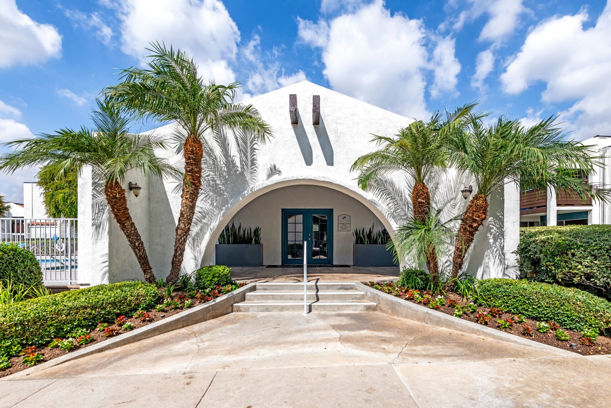 The leasing office entryway surrounded by lush palm trees at Kendallwood Apartments in Whittier, California