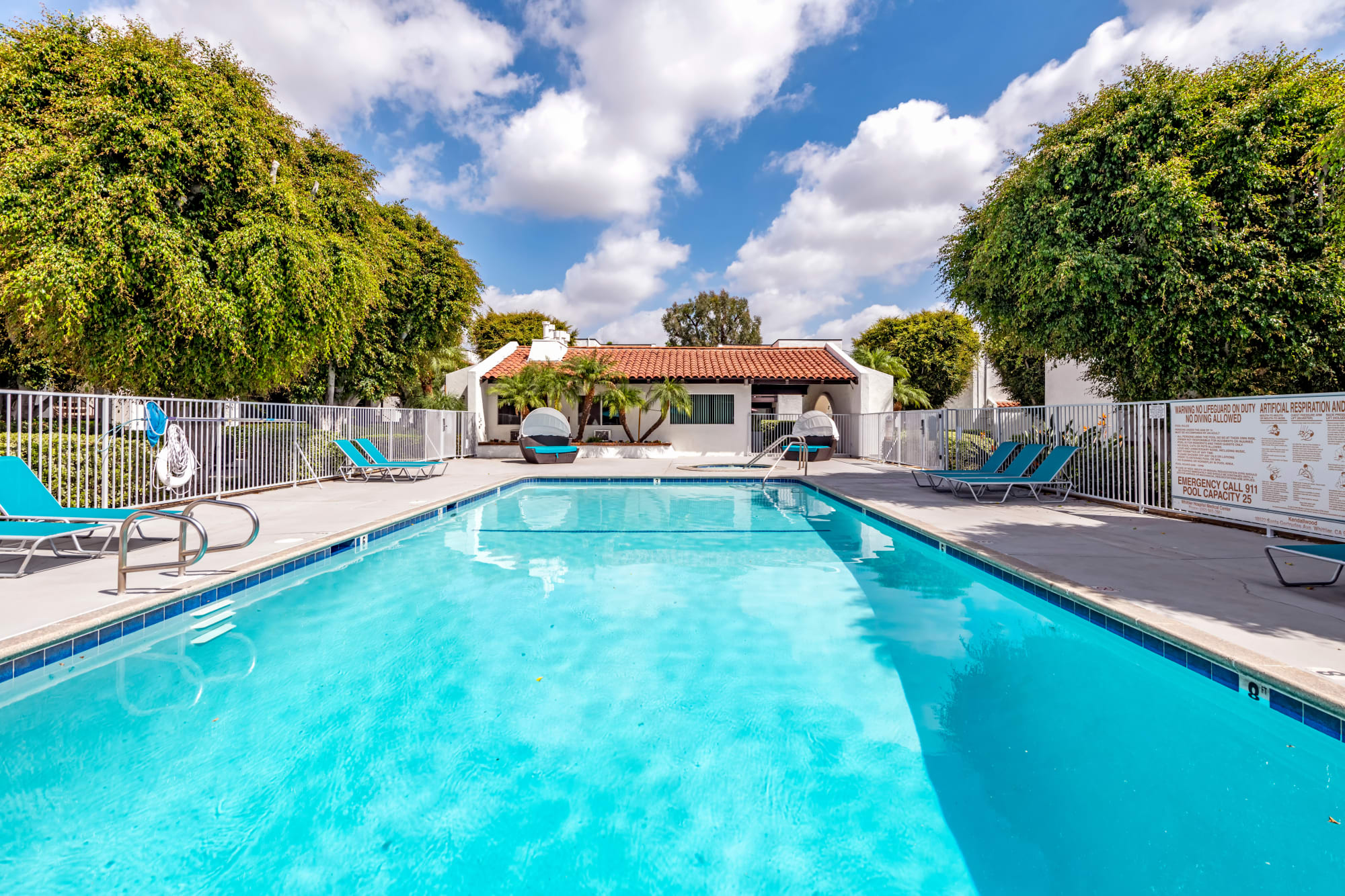 The sparkling swimming pool on a sunny day at Kendallwood Apartments in Whittier, California