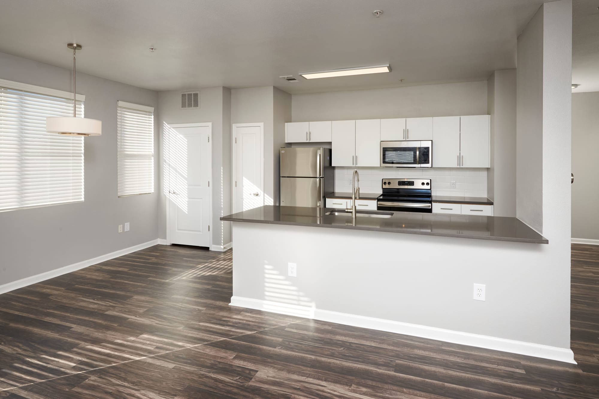 Beautiful white cabinetry renovated kitchen with stainless steel appliances and kitchen island at The Rail at Inverness in Englewood, CO