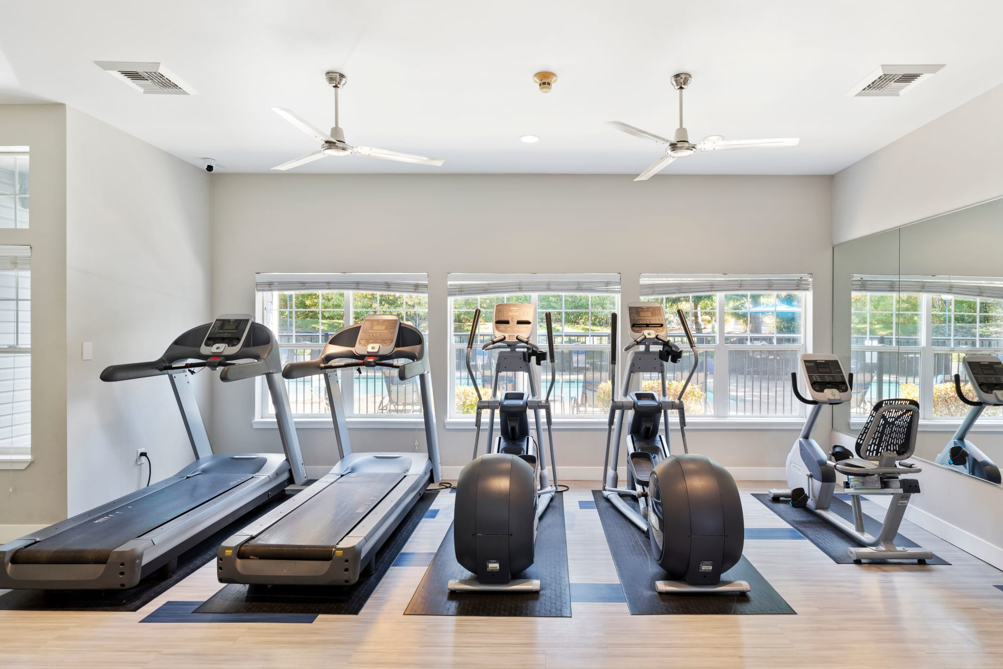 Fitness center with boxing machines and cardio at Pebble Cove Apartments in Renton