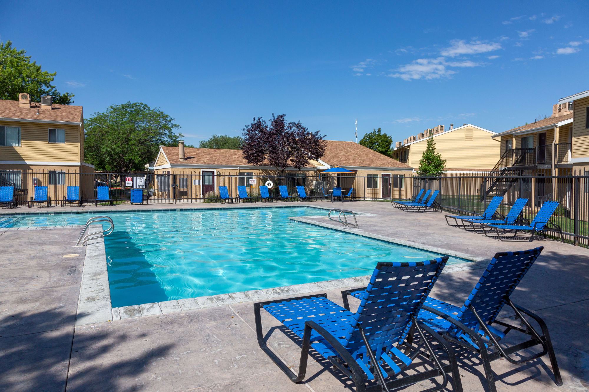 Lounge chairs by the sparkling pool at Callaway Apartments in Taylorsville, Utah