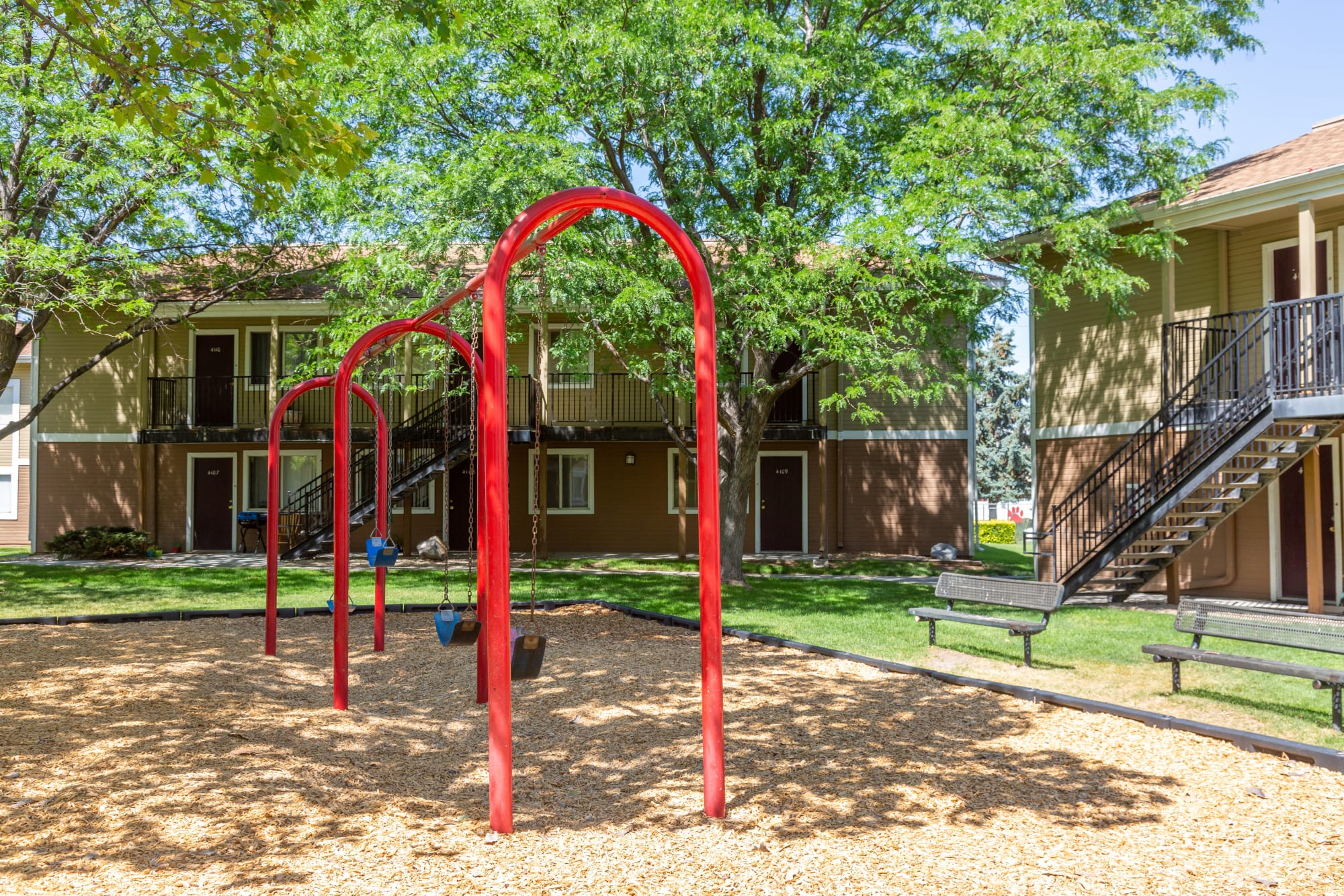 Playground surrounded by green grass at Callaway Apartments in Taylorsville, Utah