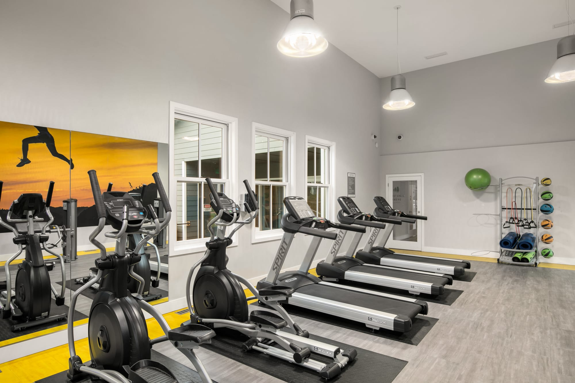 Fitness Center cardio machines with large windows looking out to pool area