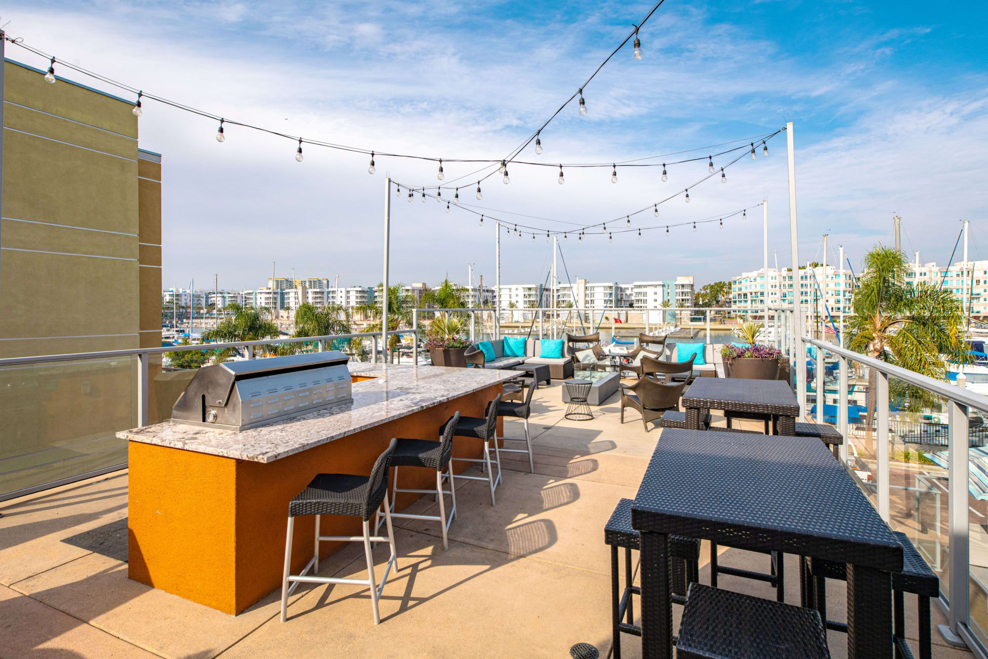 Barbecue poolside with your friends while enjoying view of the marina at Harborside Marina Bay Apartments in Marina del Rey, California