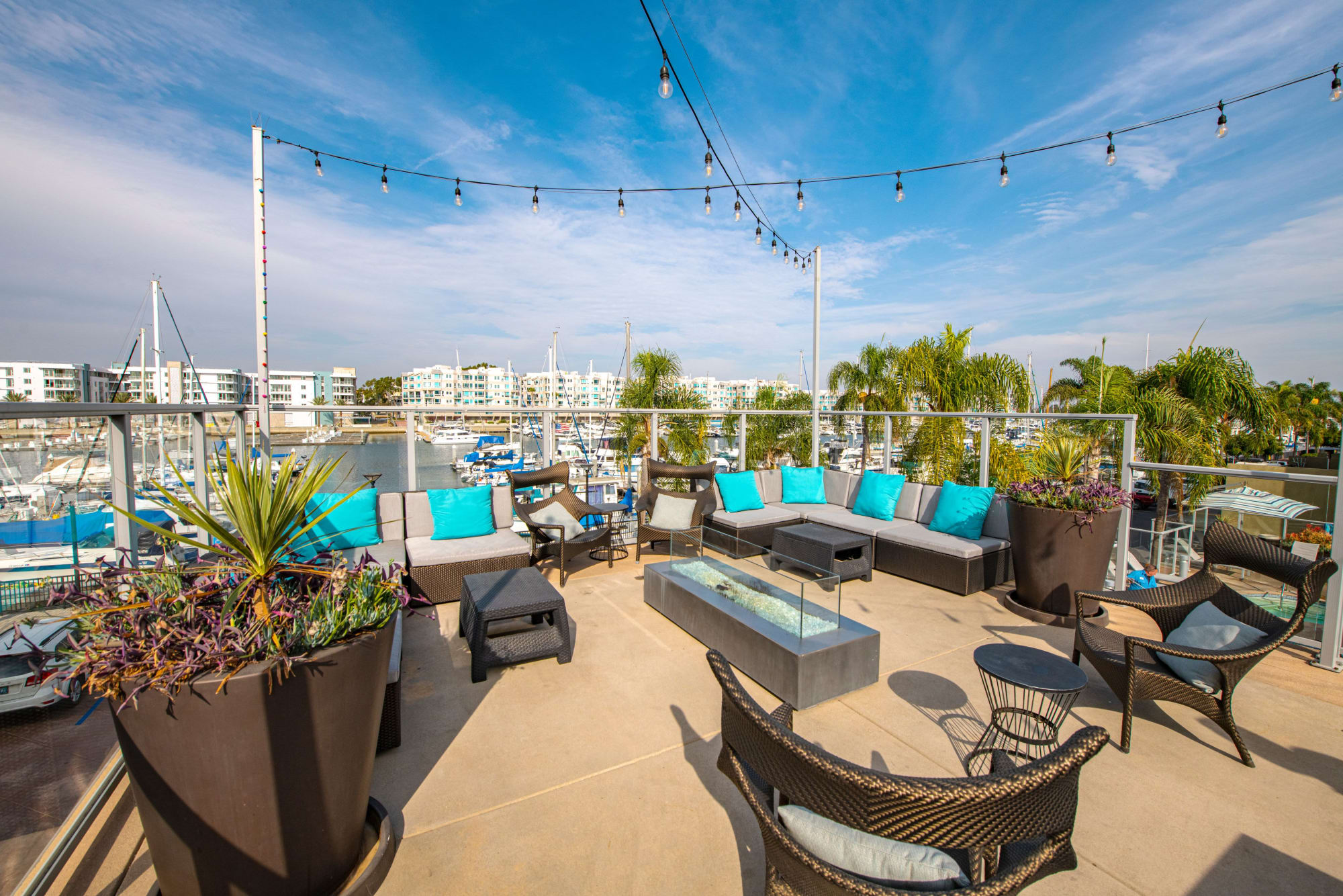 Spacious outside community area with comfortable seating and a fire pit at Harborside Marina Bay Apartments in Marina del Rey, California