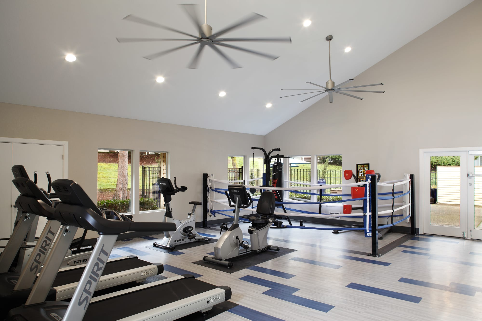 Fitness center with cardio machines and a boxing ring at Park South Apartments in Seattle, Washington
