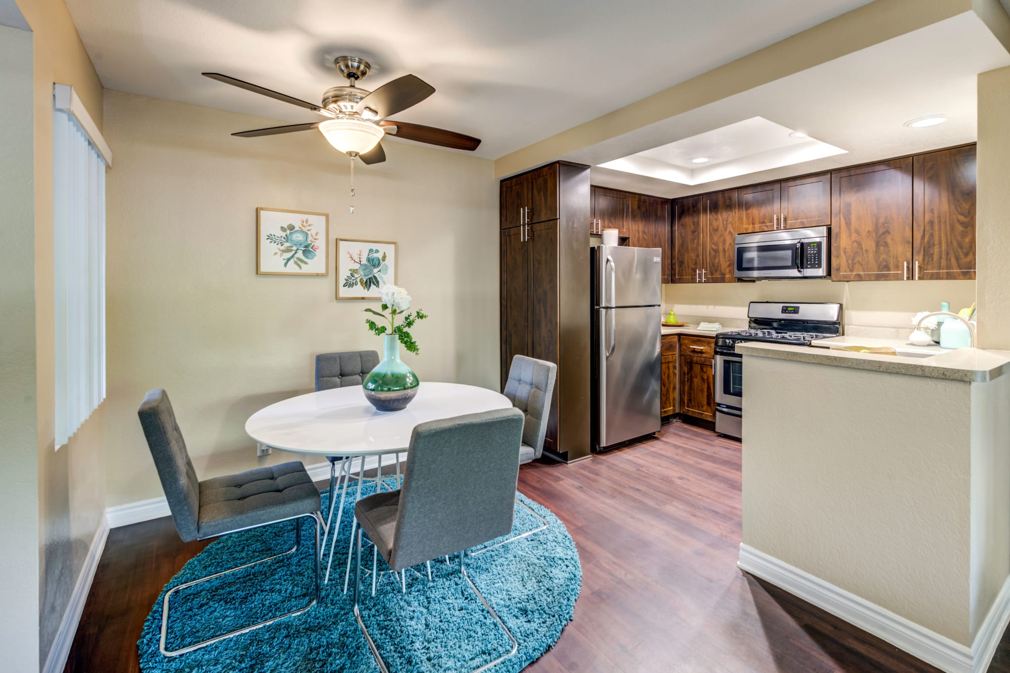 Renovated kitchen with brown cabinets and dining area at Village Oaks in Chino Hills, California