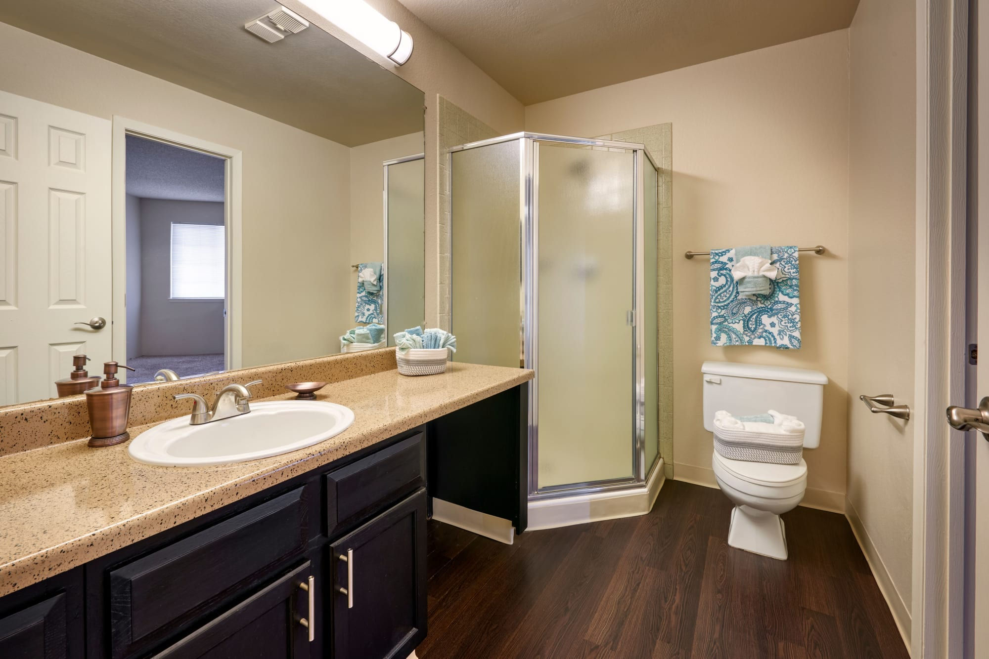 Recently renovated bathroom with brown cabinets at Bluesky Landing Apartments in Lakewood, Colorado