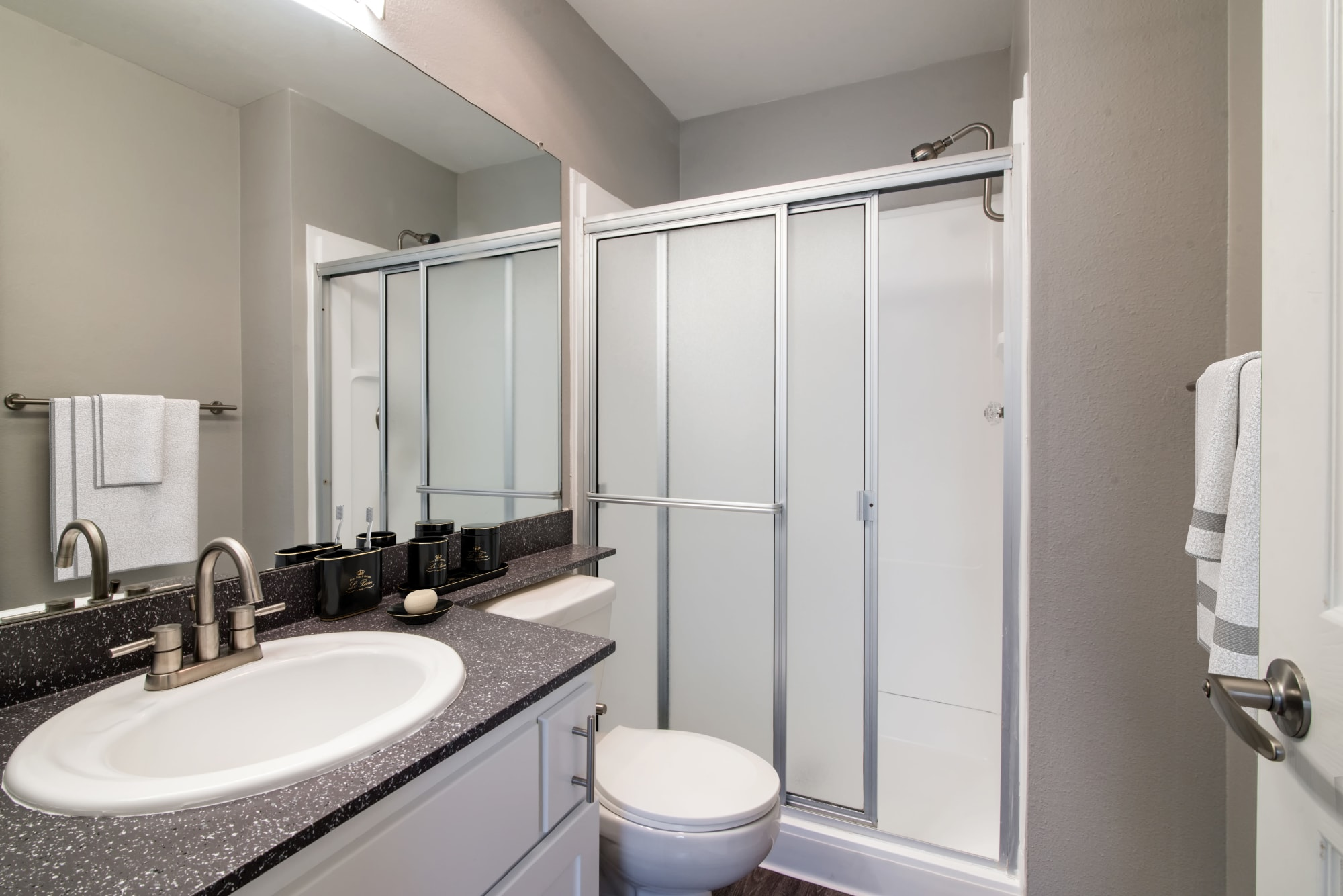 A renovated bathroom with white cabinets at Lakeview Village Apartments in Spring Valley, California