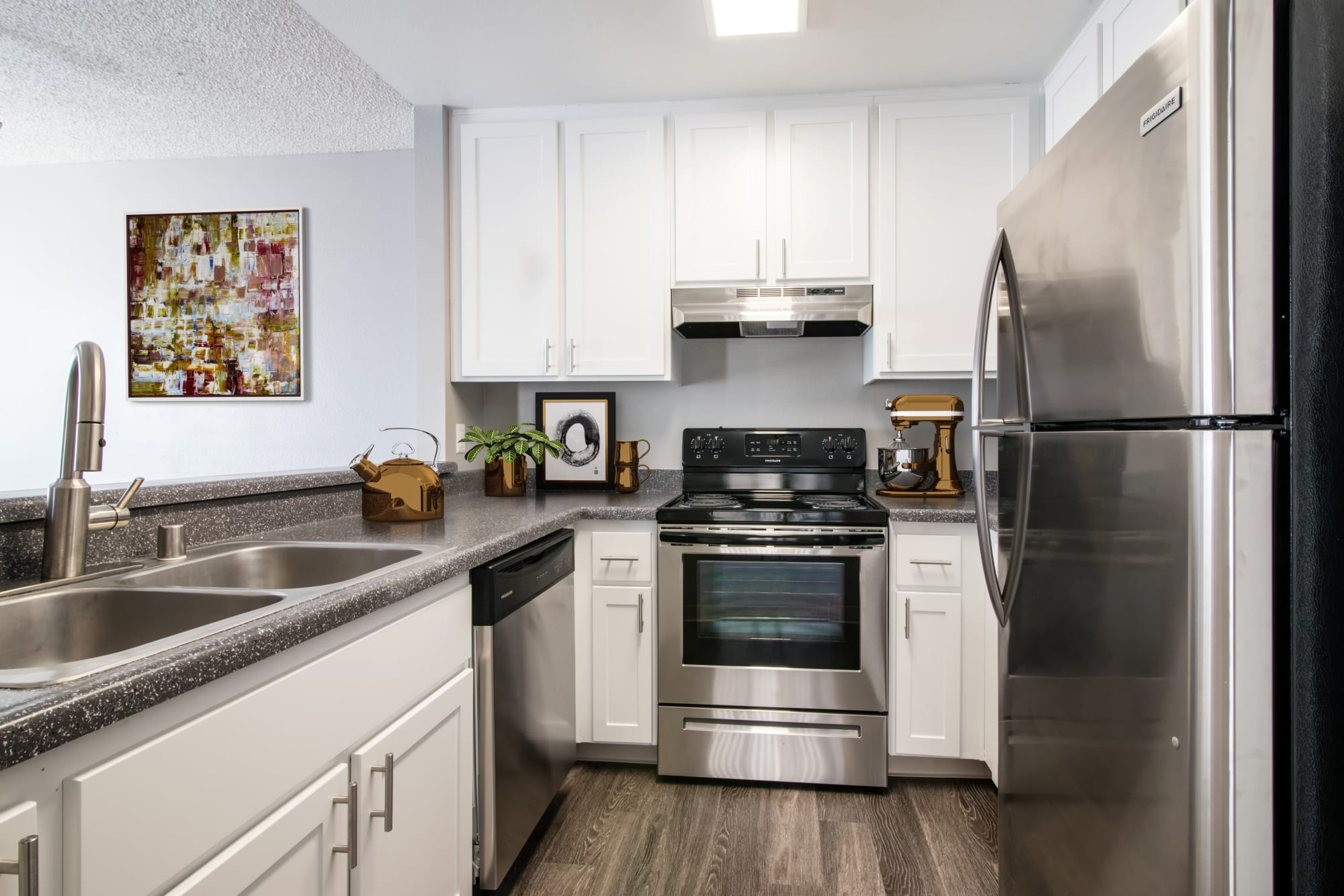 Renovated kitchen with white cabinets and stainless steel appliances at Lakeview Village Apartments in Spring Valley, California