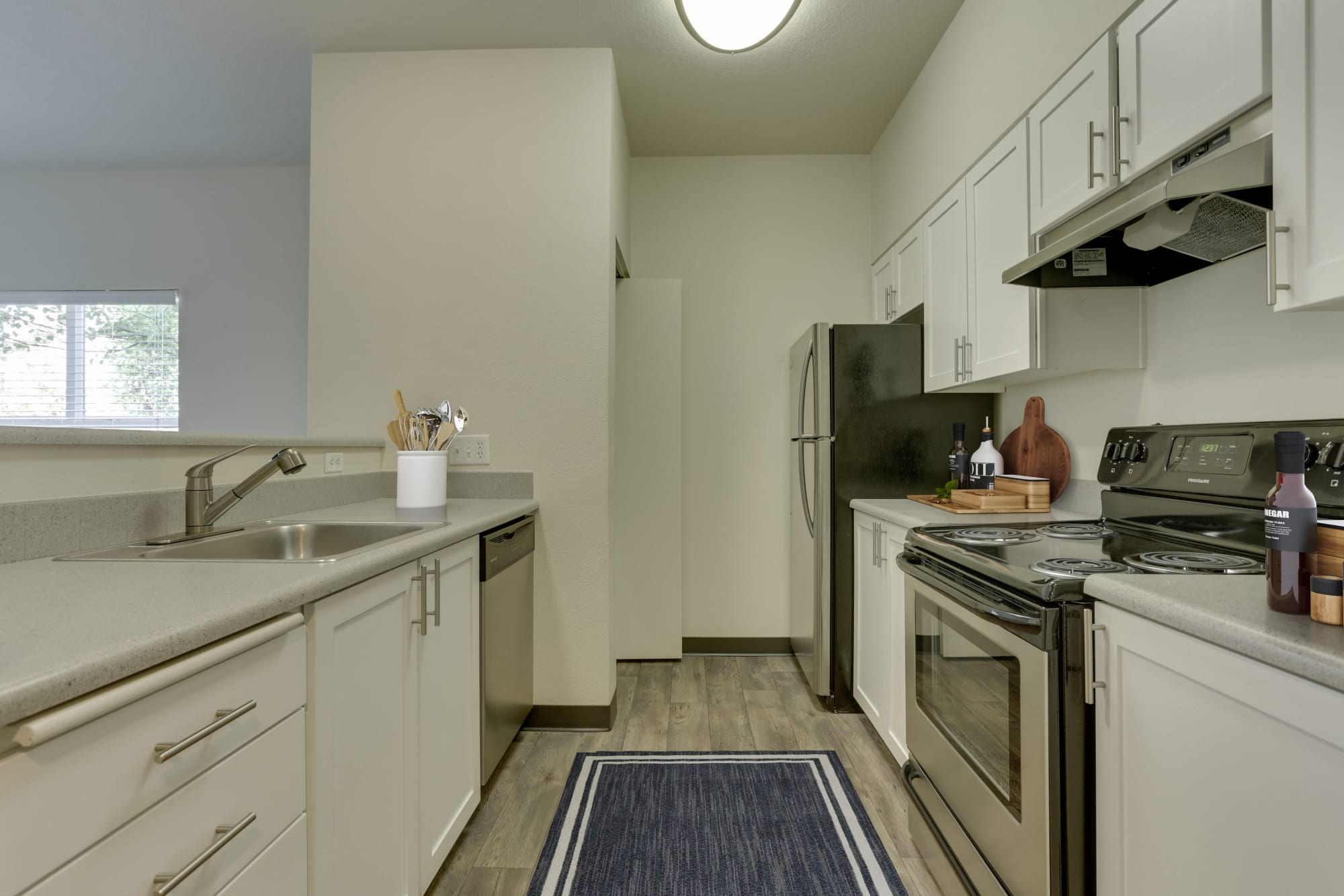 Newly renovated kitchen with white cabinets and stainless steel appliances at The Landings at Morrison Apartments in Gresham, Oregon