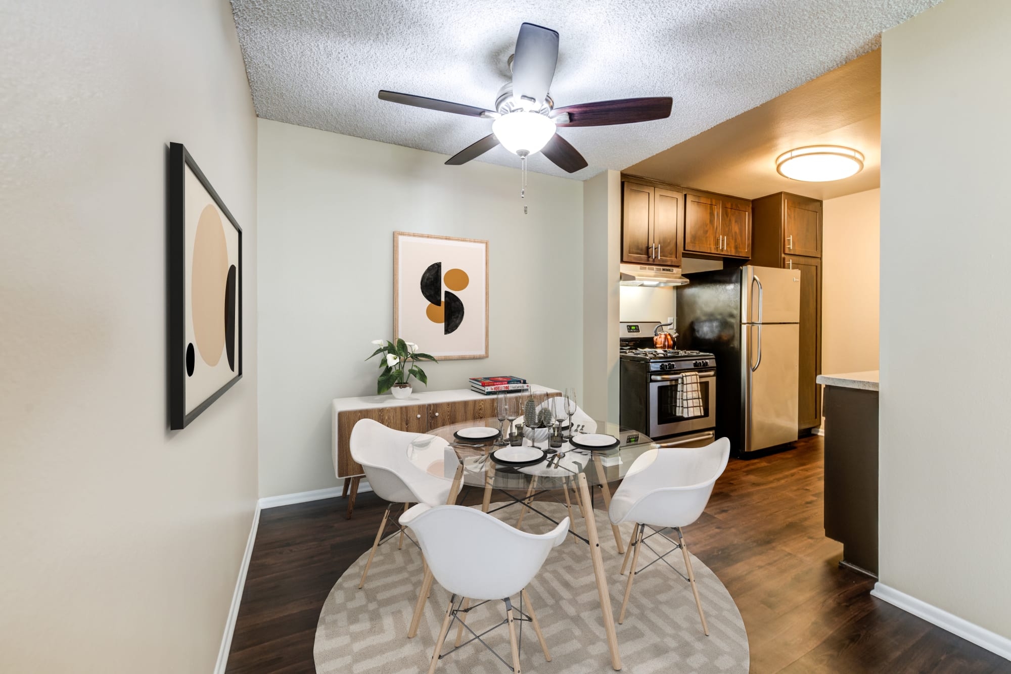 Dining room and kitchen with hardwood-style floors at Kendallwood Apartments in Whittier, California