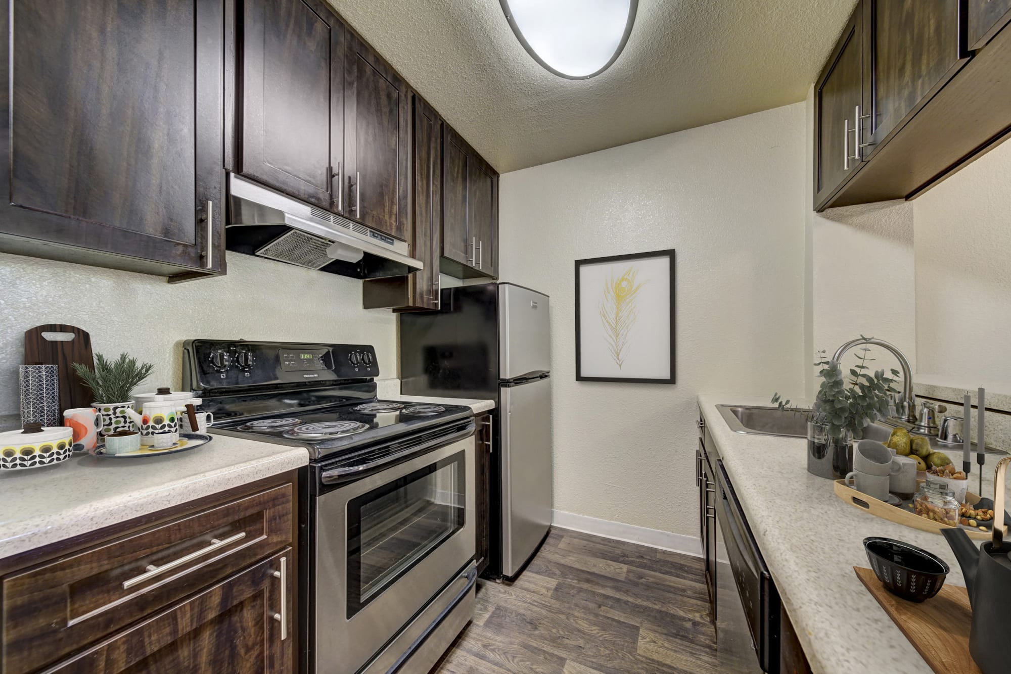 Renovated brown kitchen with stainless steel appliances at The Timbers Apartments in Hayward, California