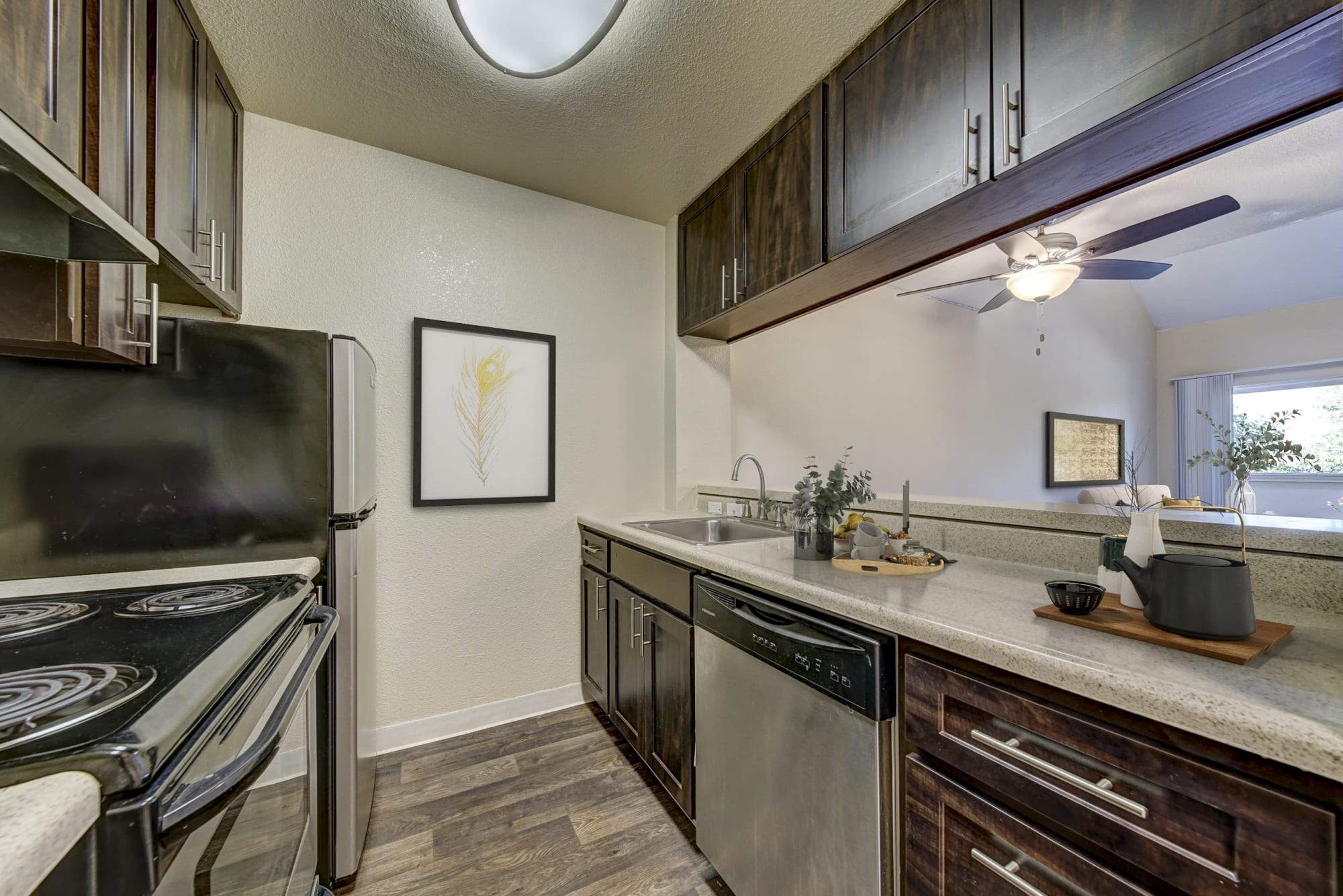 Renovated Brown Kitchen with stainless steel appliances at The Timbers Apartments in Hayward, CA