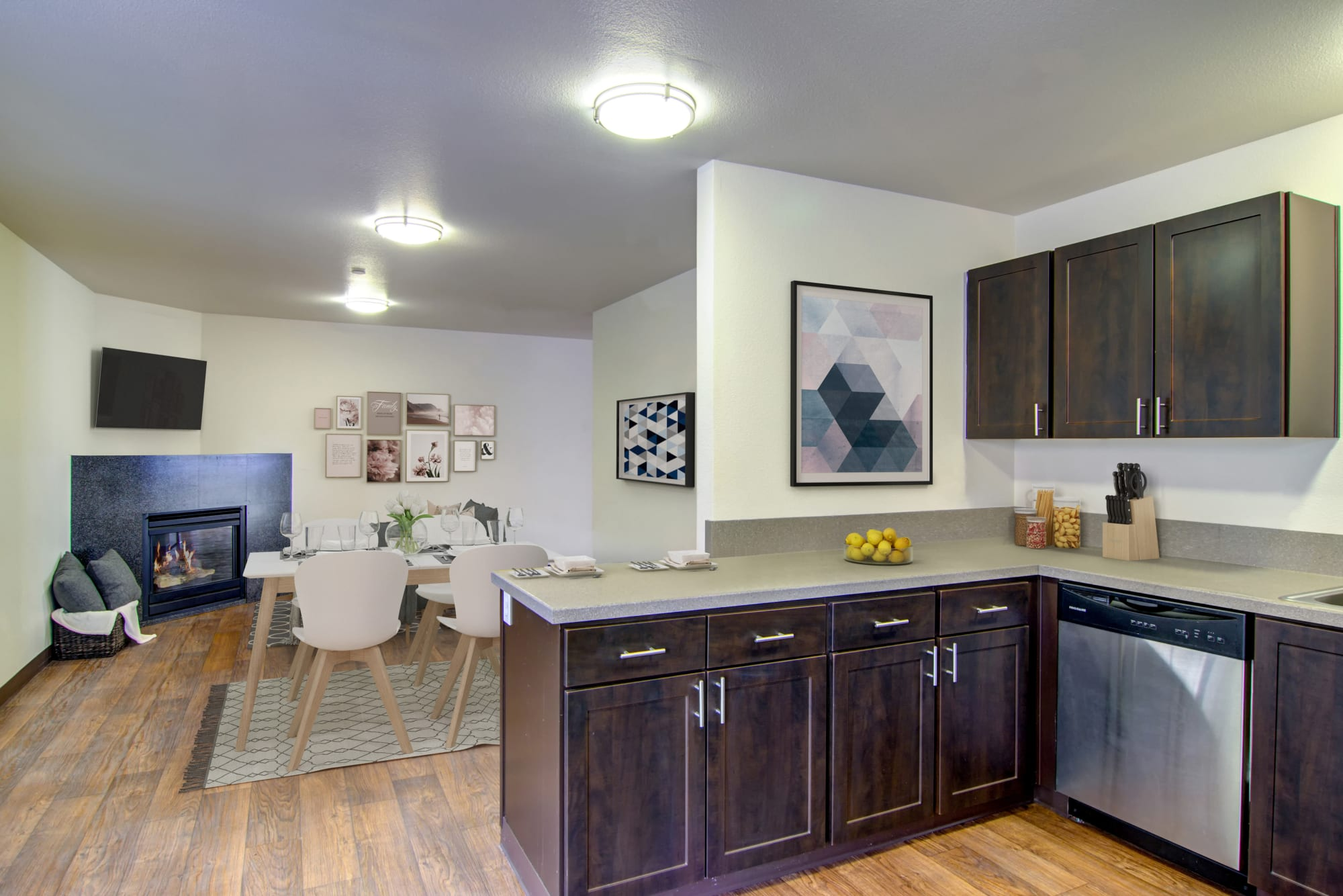 Renovated kitchen looking into a dining room with a fireplace at The Addison Apartments in Vancouver, Washington