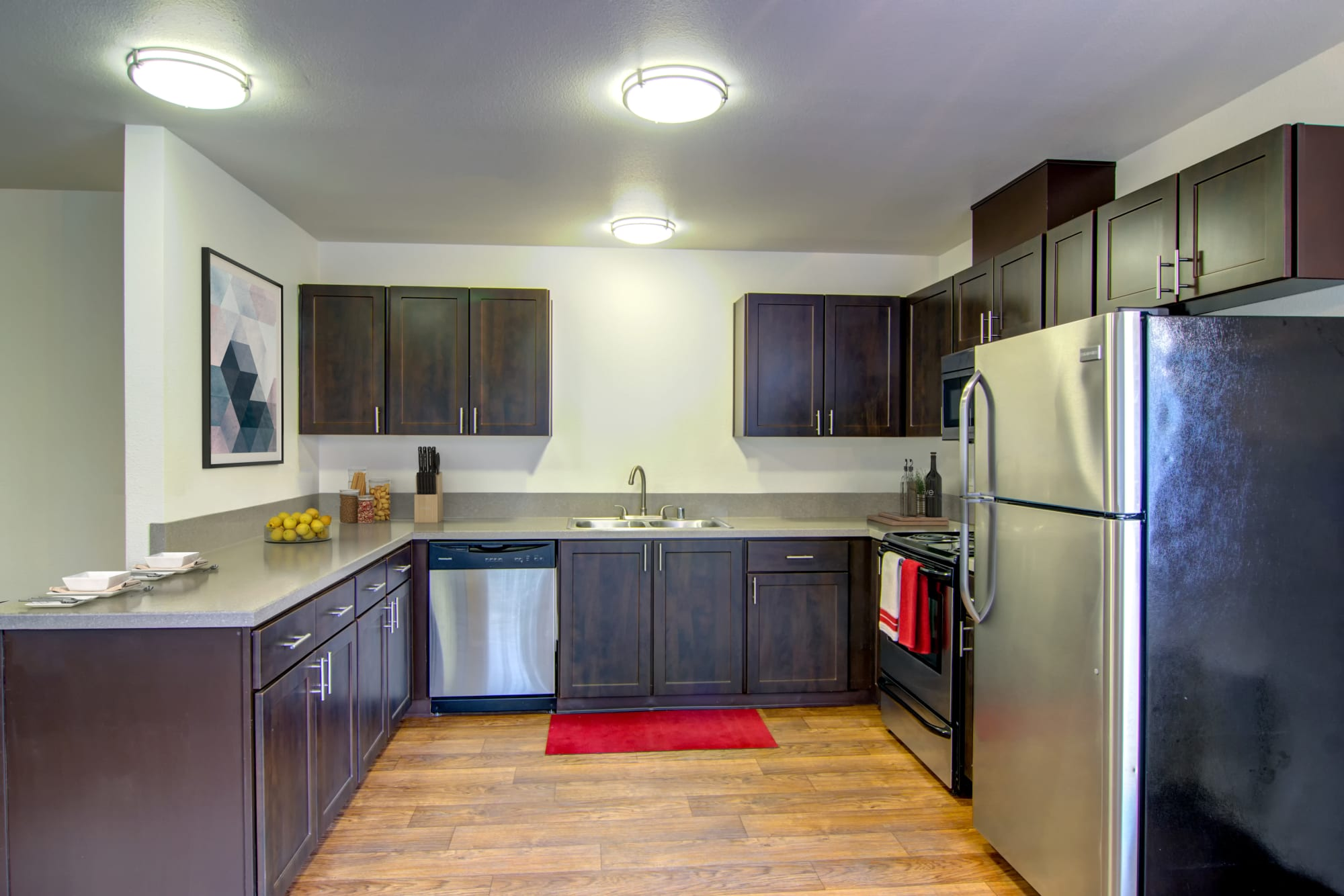 Renovated kitchen with brown cabinets and stainless steel appliances at The Addison Apartments in Vancouver, Washington