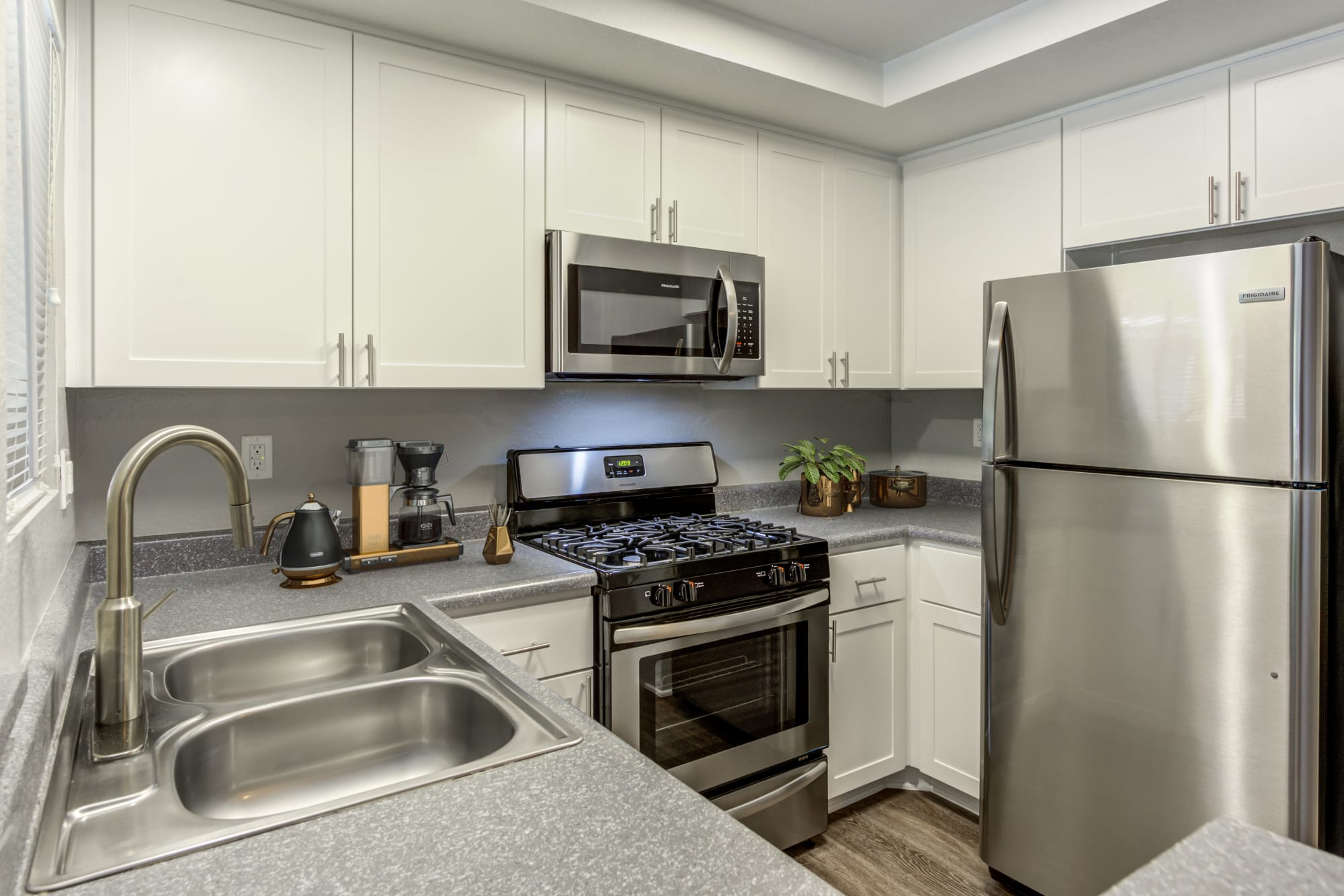 Renovated kitchen with white cabinets and stainless steel appliances at Village Oaks in Chino Hills, California
