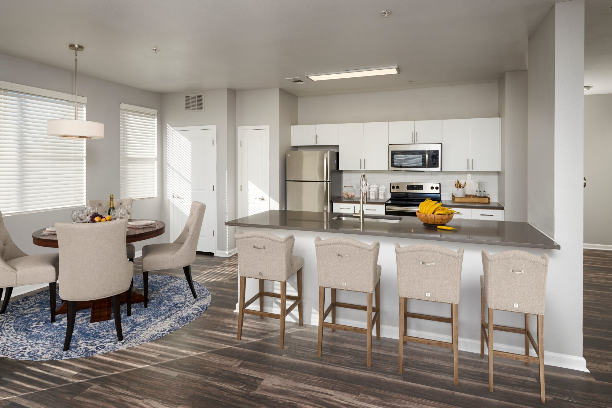 Beautiful white cabinetry in a renovated kitchen with stainless steel appliances and a kitchen island at The Rail at Inverness in Englewood, Colorado