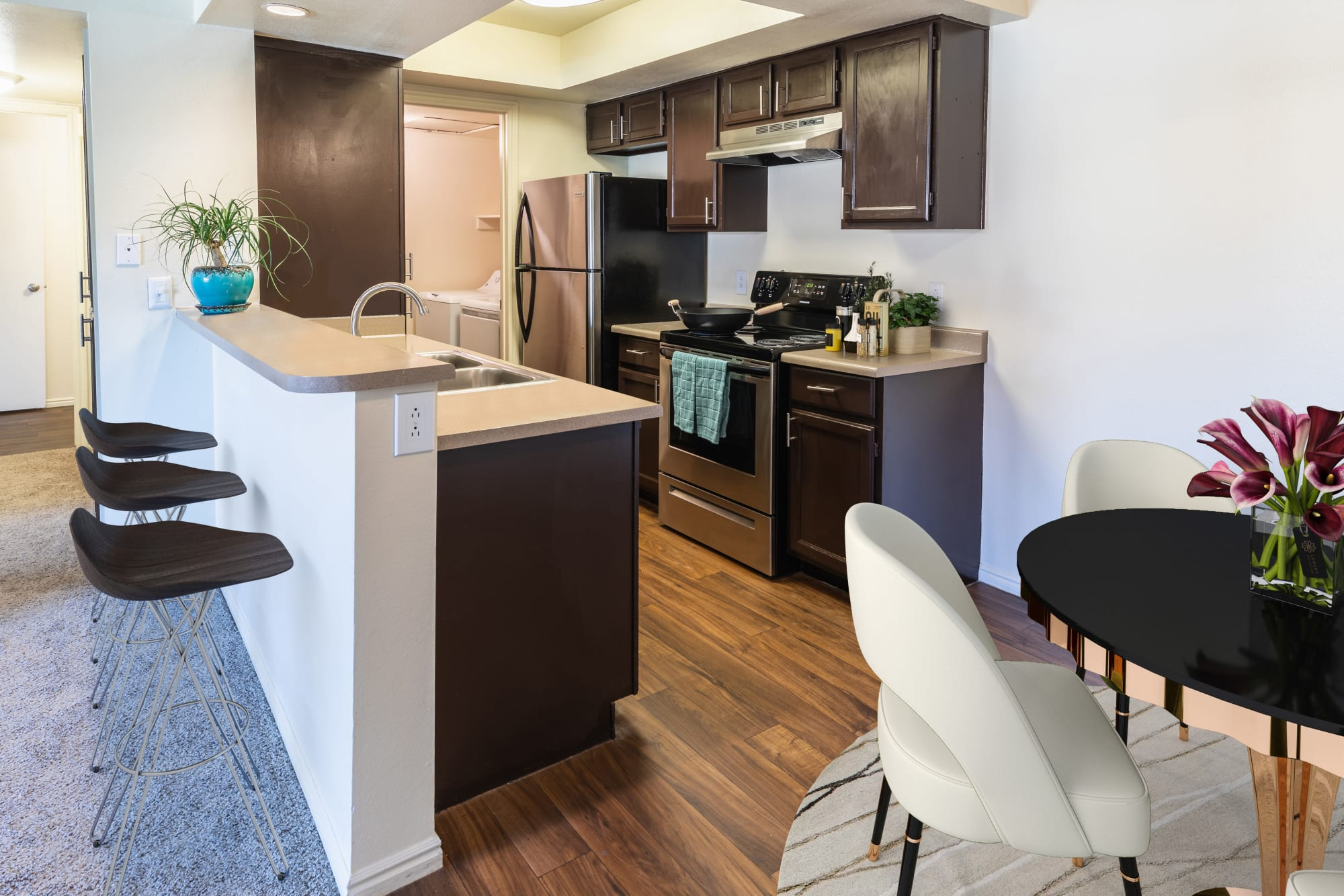 Fully equipped renovated brown kitchen and dining room with stainless steel appliances at Shadowbrook Apartments in West Valley City, Utah