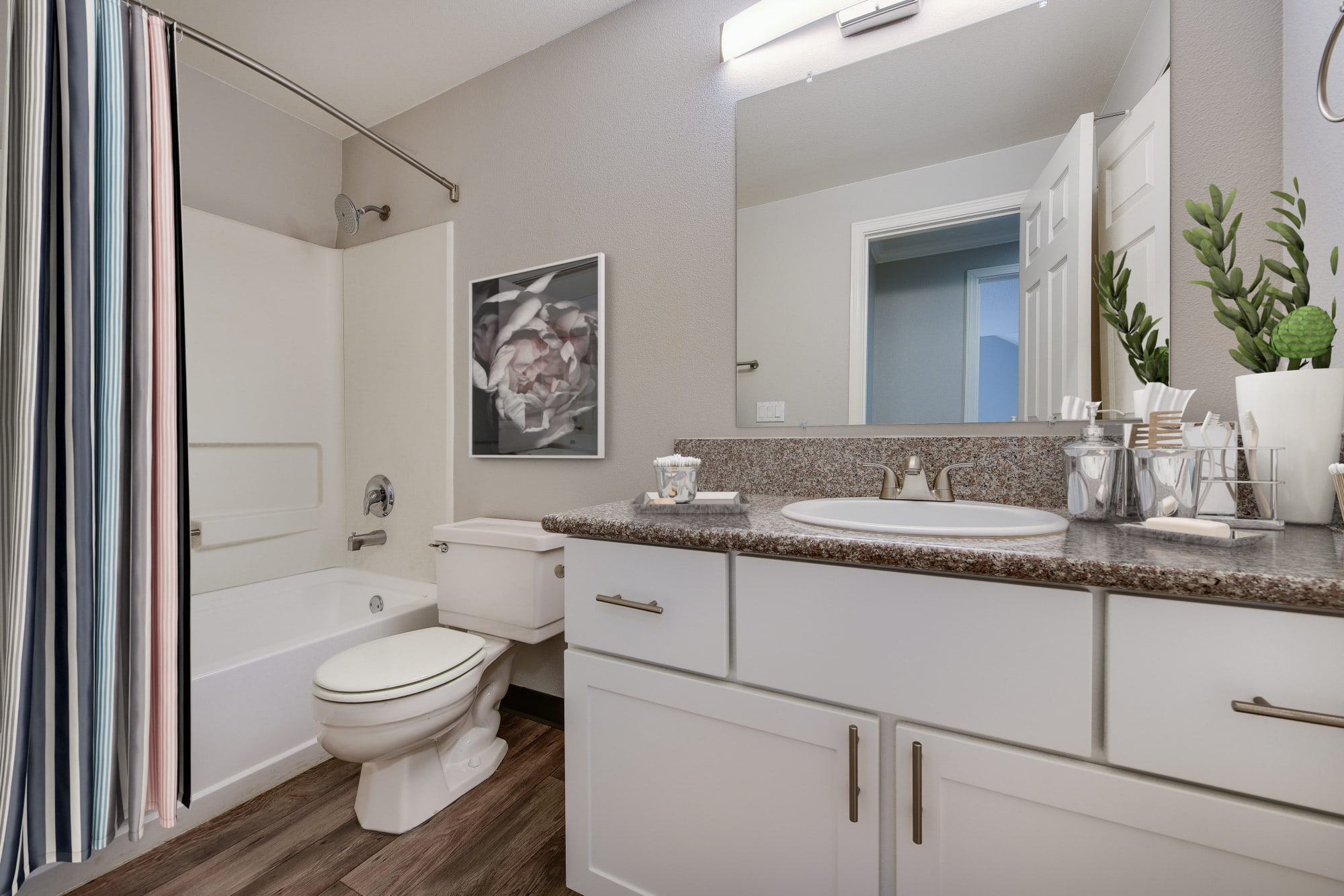 Renovated bathroom with white cabinets and a tub at Walnut Grove Landing Apartments in Vancouver, Washington