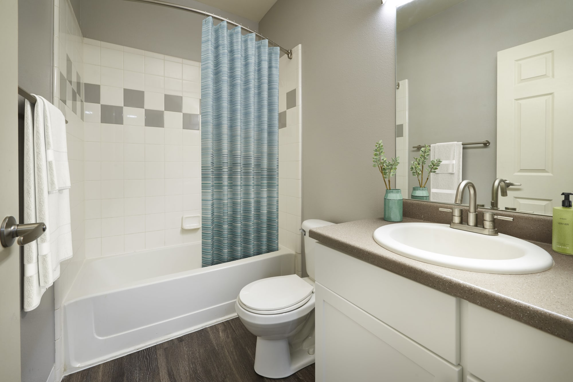 Bathroom with white cabinets and a tub at Westridge Apartments in Aurora, Colorado