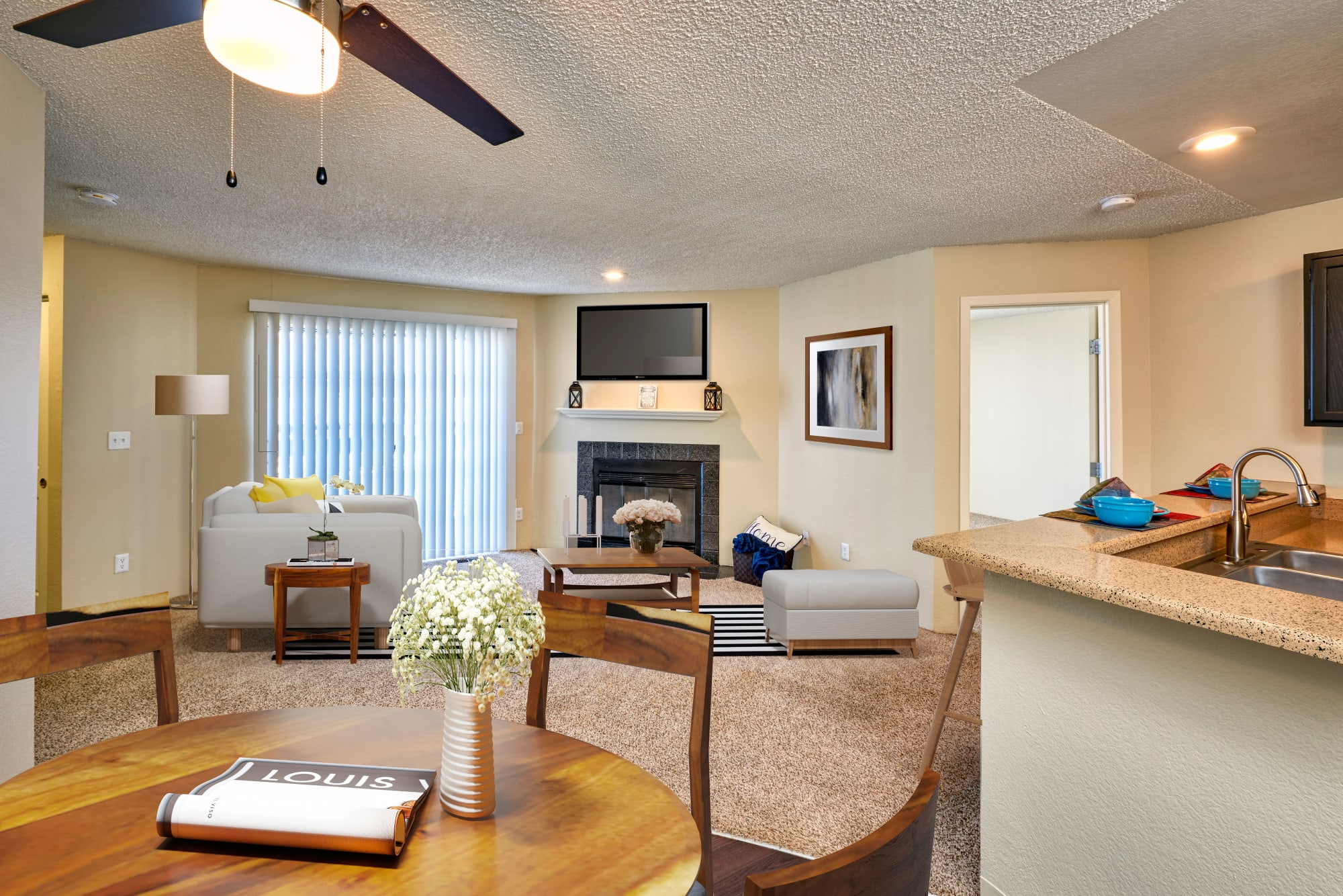 Living room with a fireplace and patio door at Bluesky Landing Apartments in Lakewood, Colorado