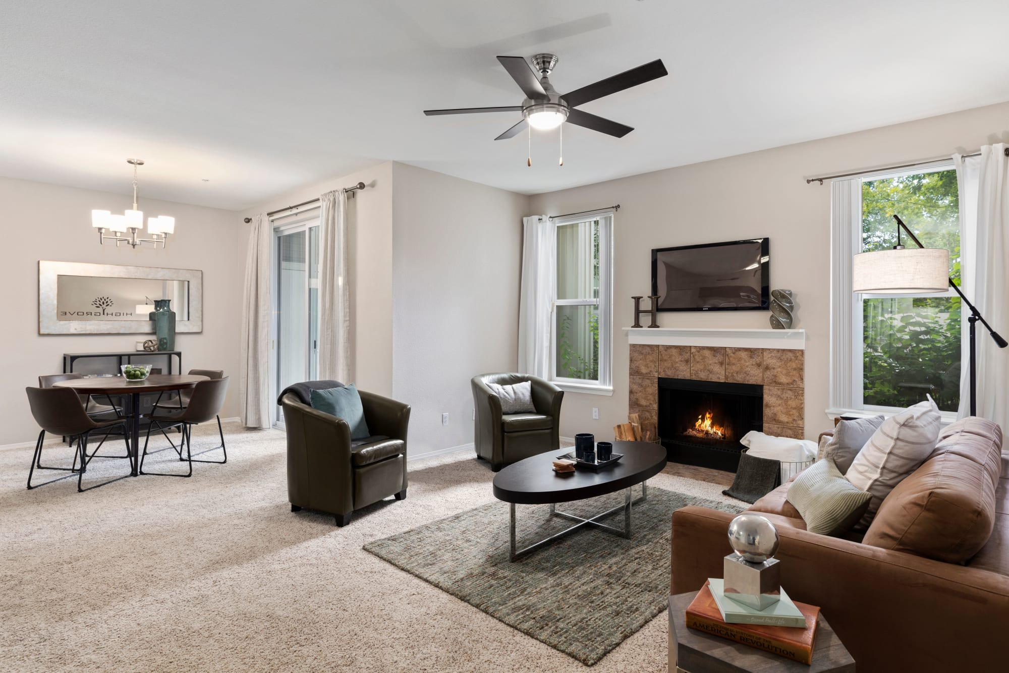 Living room with a fireplace and a view of the dining room at HighGrove Apartments in Everett, Washington