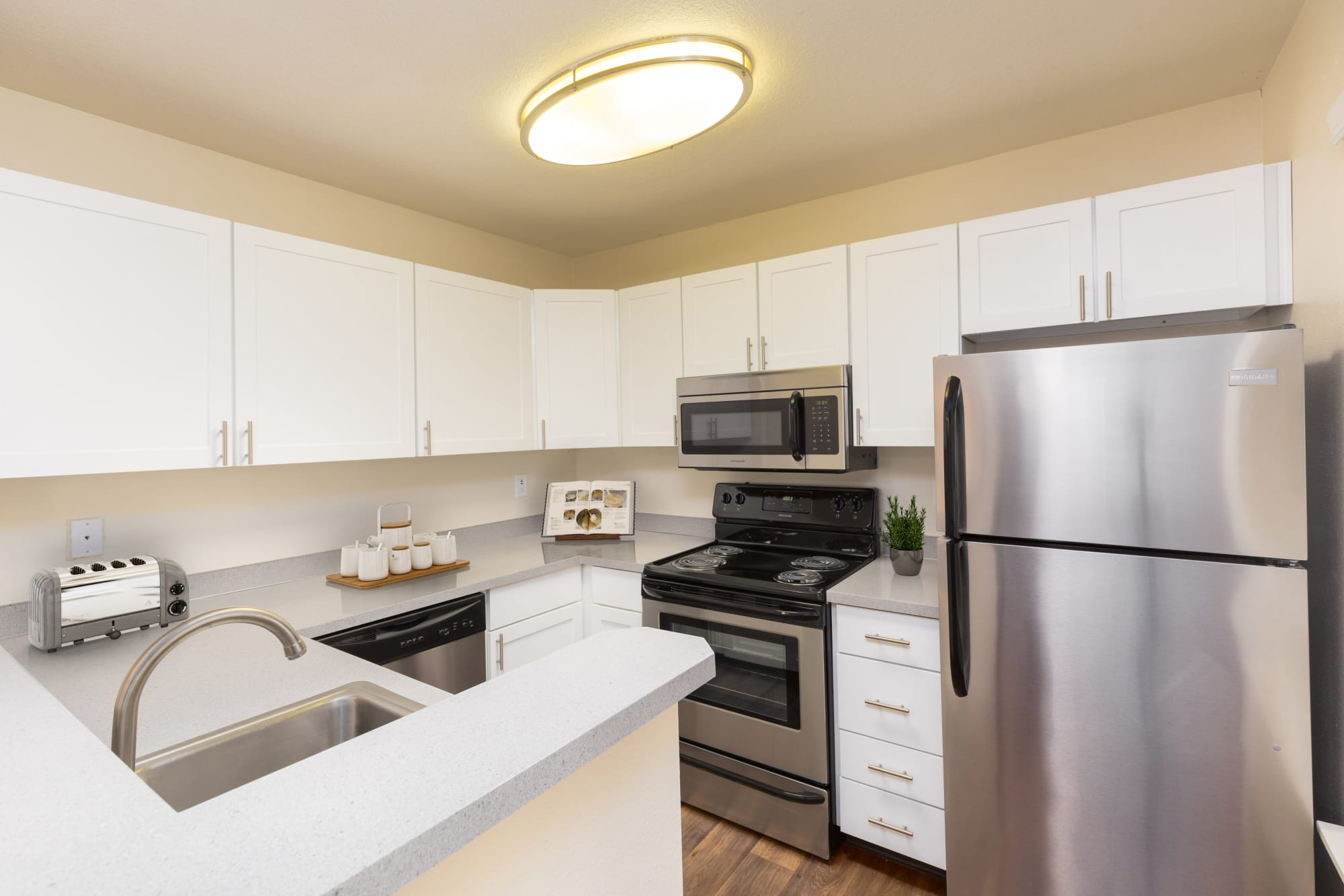 Updated kitchen with white cabinets at Autumn Chase Apartments in Vancouver, Washington