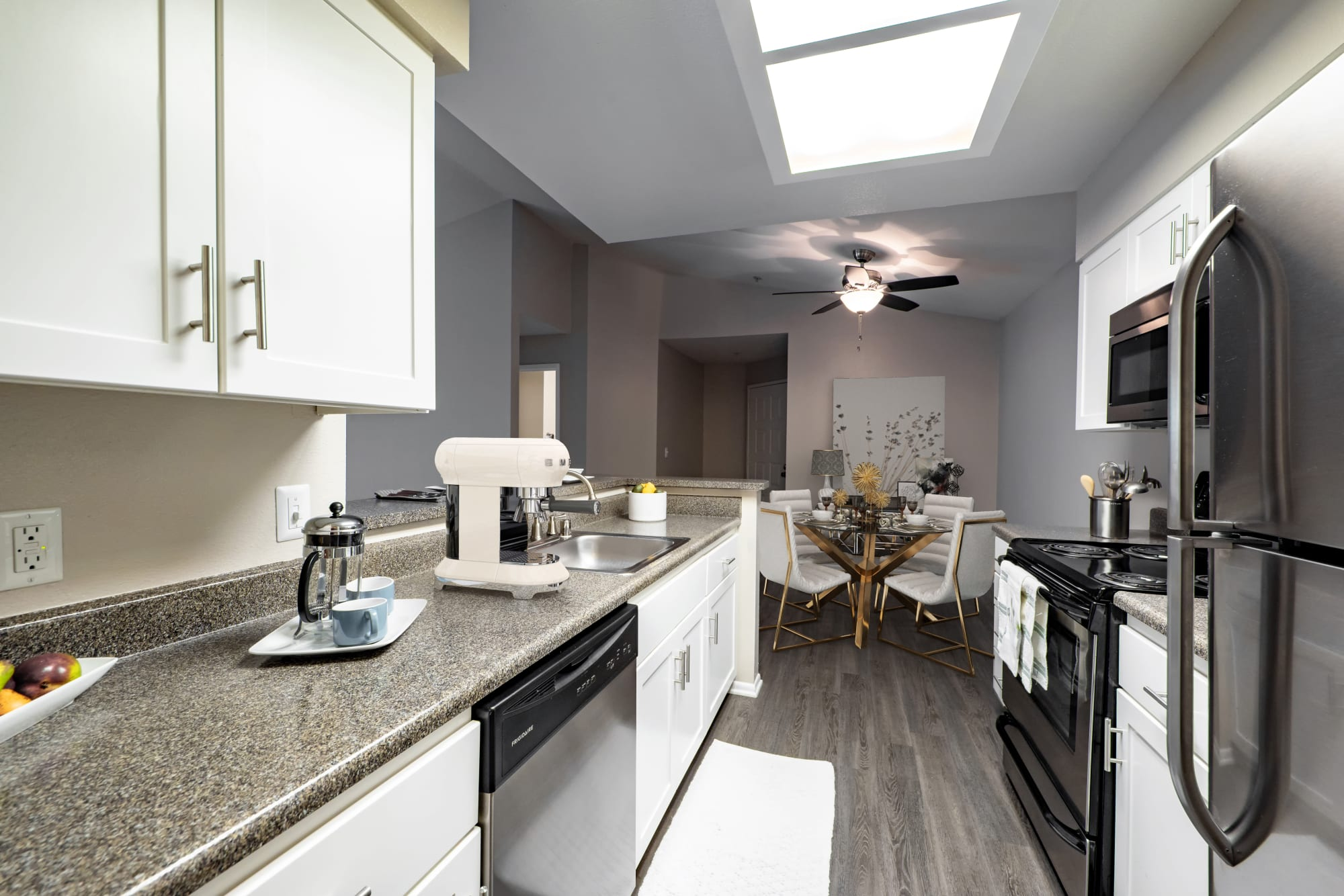 White renovated model kitchen with stainless steel appliances at Sierra Del Oro Apartments in Corona, California