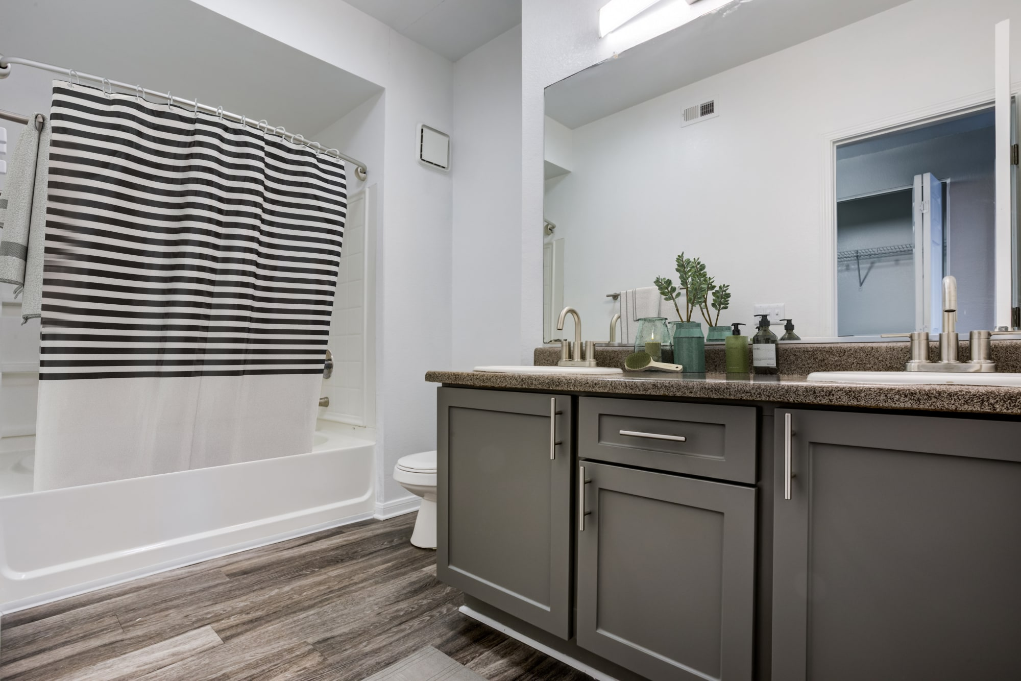 A well decorated bathroom with grey cabinets at Miramonte and Trovas in Sacramento, California
