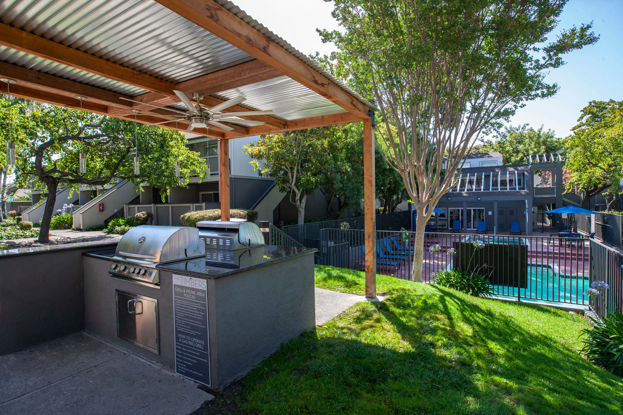 Covered outdoor BBQ at The Timbers Apartments in Hayward, California