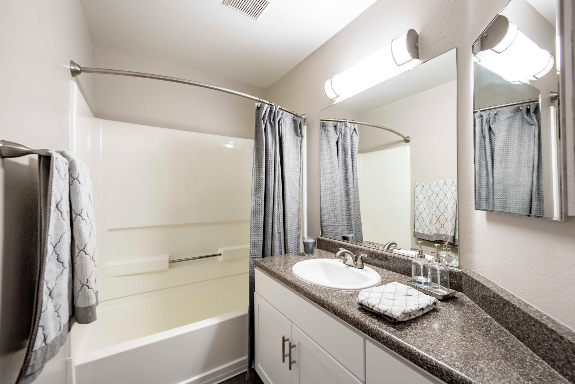 Renovated brown bathroom with a tub at Sierra Del Oro Apartments in Corona, California