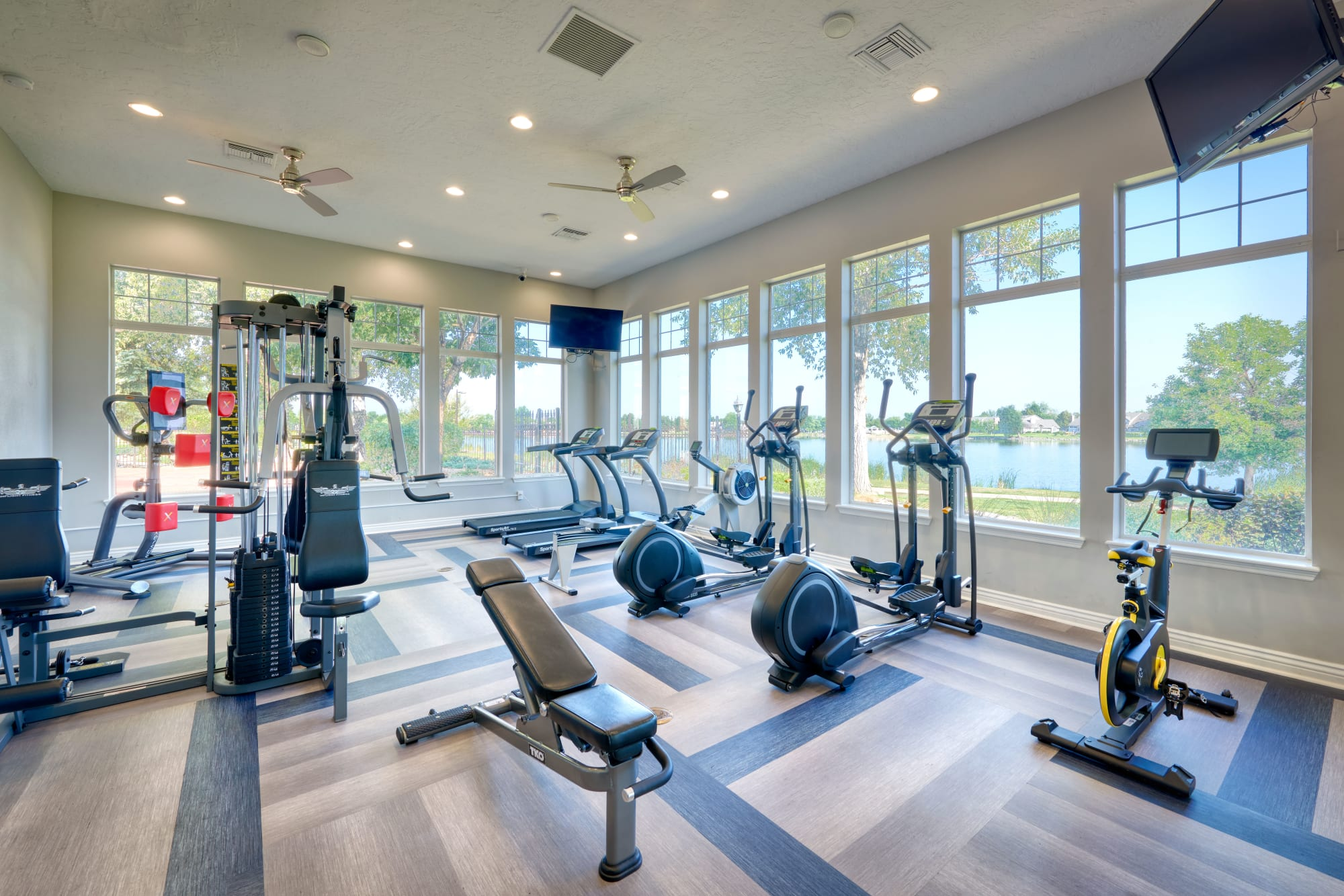 Fully equipped fitness center with lake views at Promenade at Hunter's Glen Apartments in Thornton, Colorado