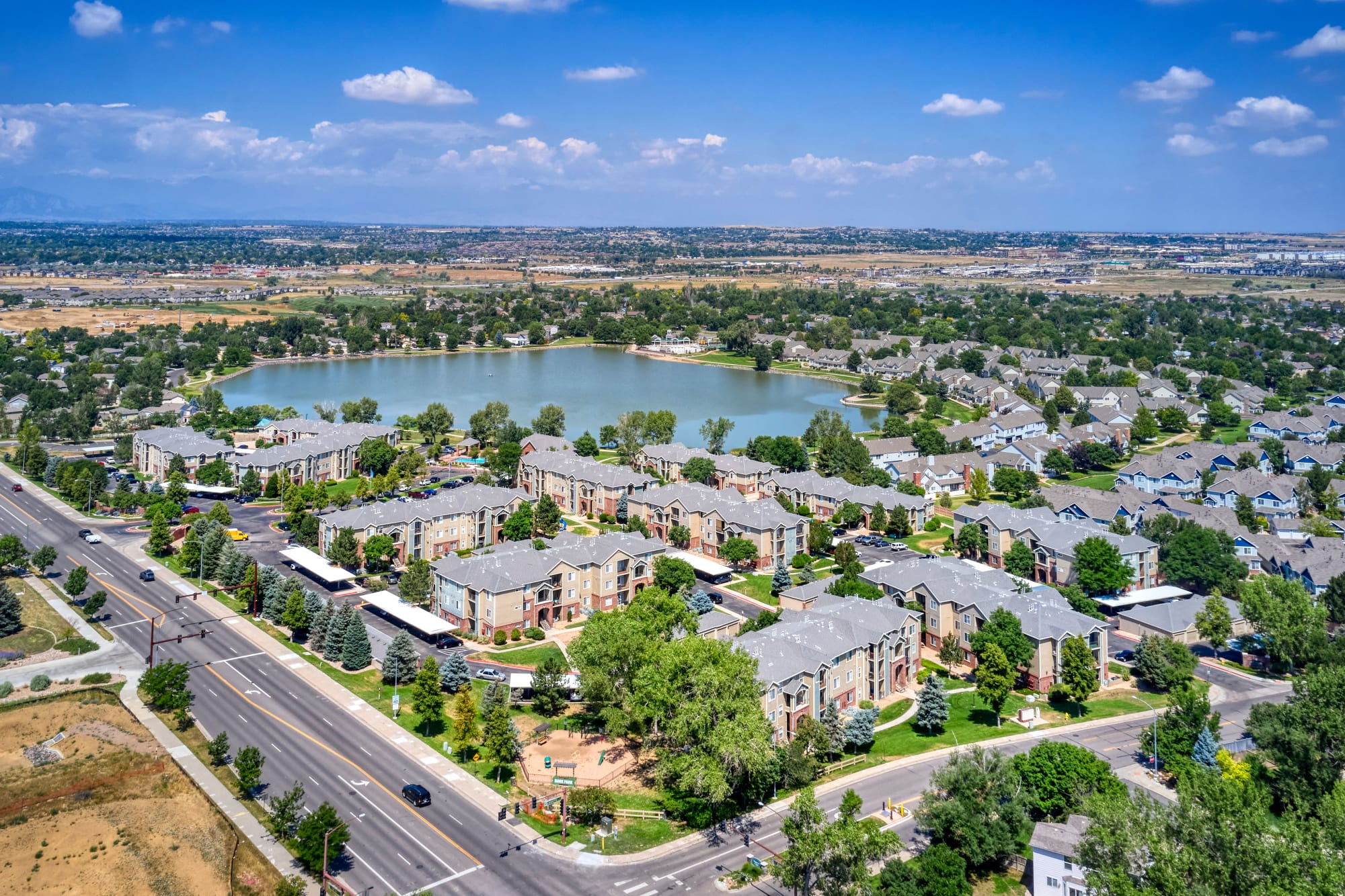 Aerial view of the lake, leasing office, and pool at Promenade at Hunter's Glen Apartments in Thornton, Colorado