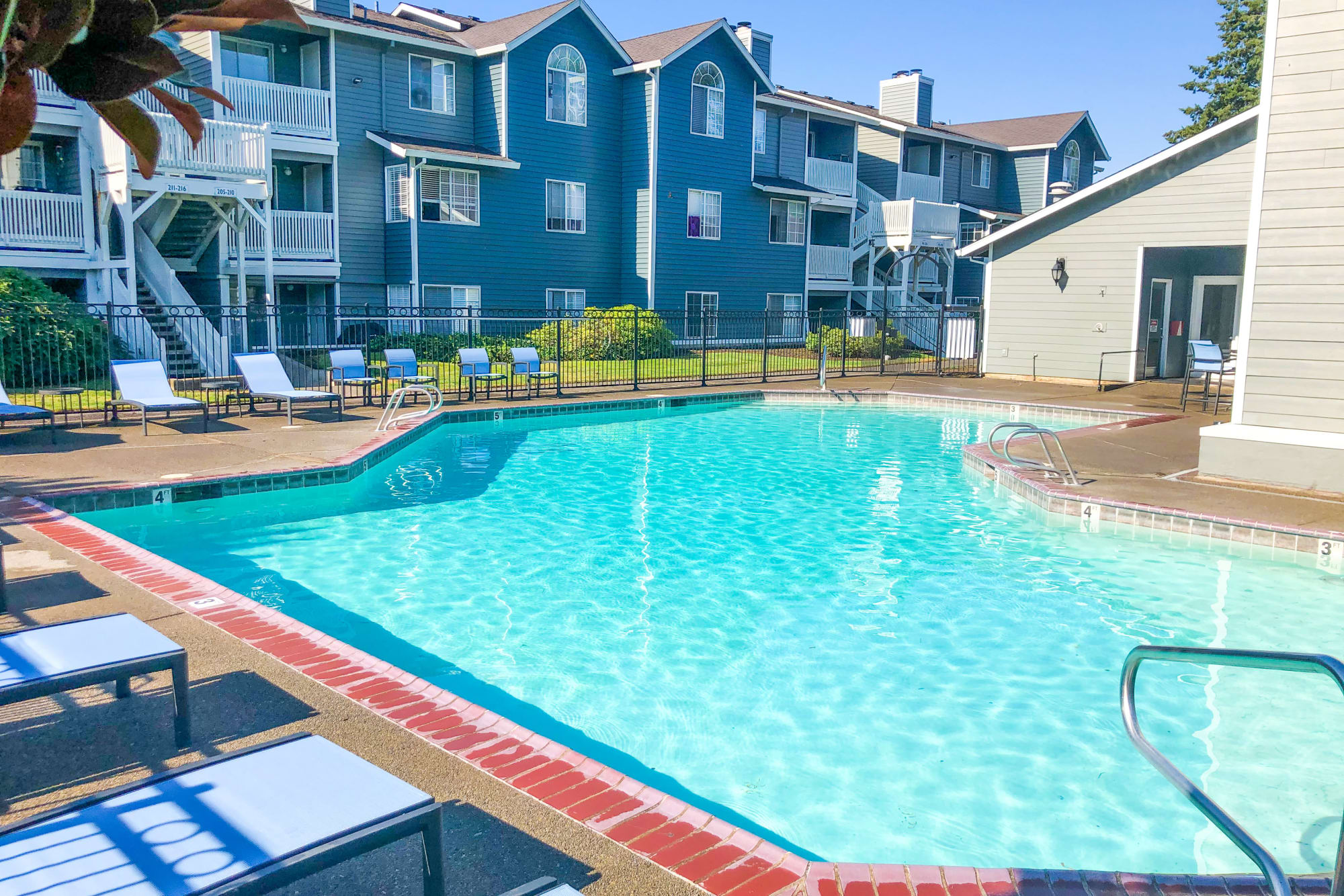 Sparkling pool with new lounge chairs at Walnut Grove Landing Apartments in Vancouver, Washington