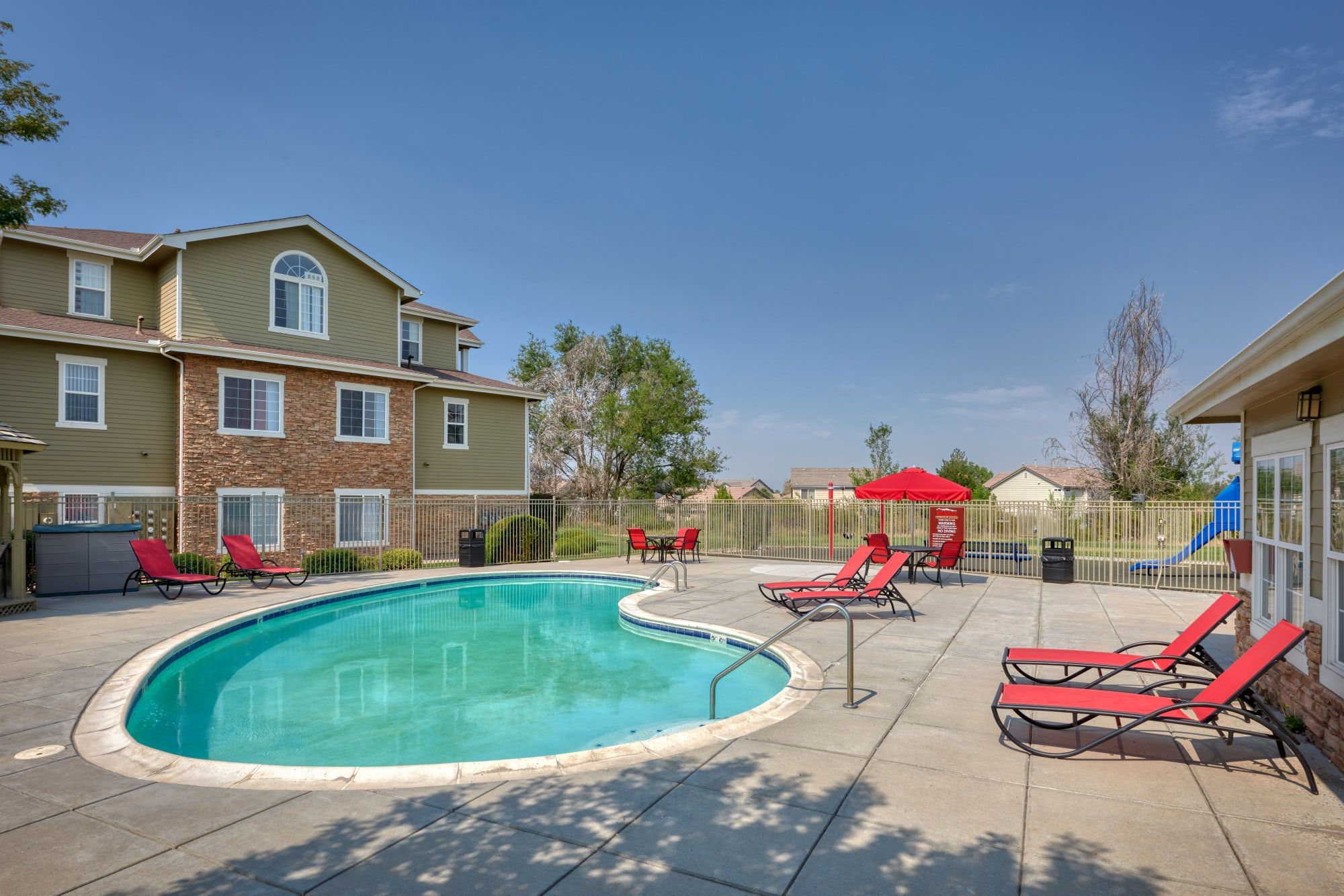 Pool and spa with lounge chairs and umbrellas at Westridge Apartments in Aurora, Colorado