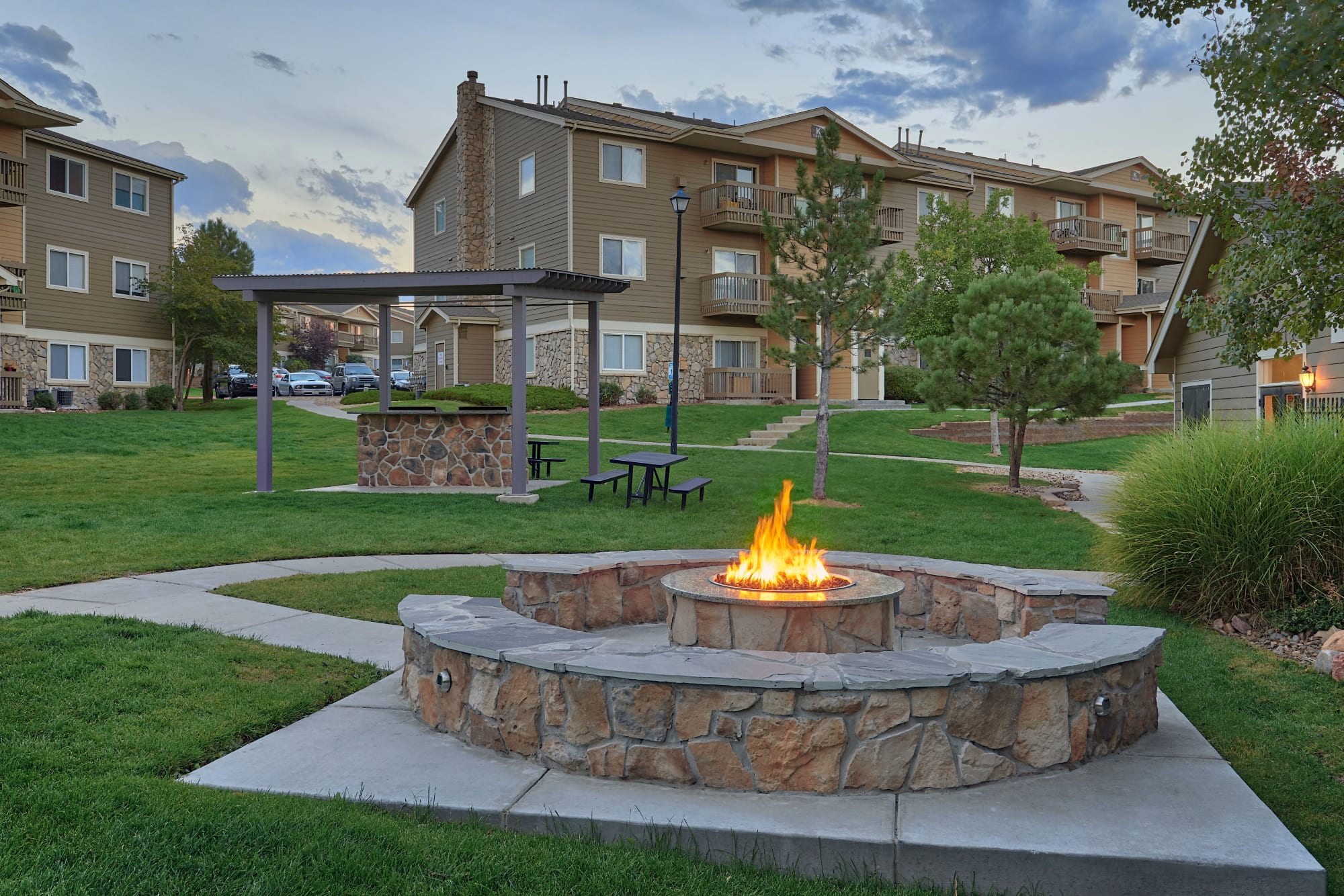 Covered barbecue area and fire pit at sunset at Crossroads at City Center Apartments in Aurora, Colorado