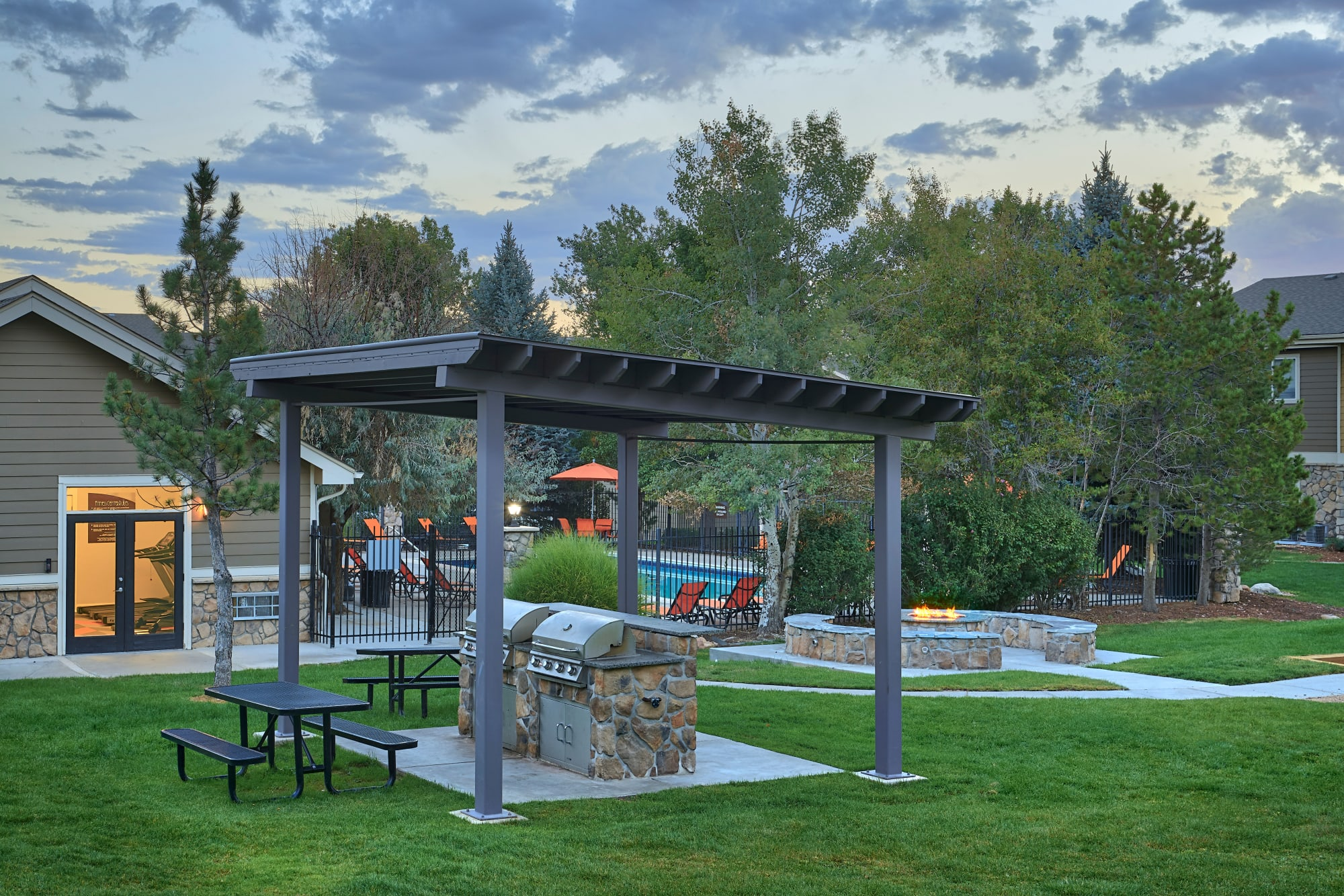 The fire pit lounge and covered bbq area at Crossroads at City Center Apartments in Aurora, Colorado