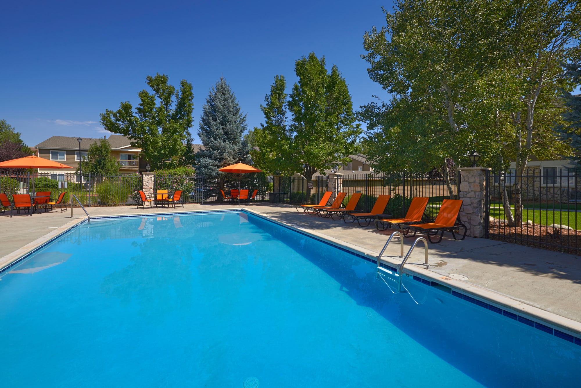 Pool with lounge chairs and umbrellas at Crossroads at City Center Apartments in Aurora, Colorado