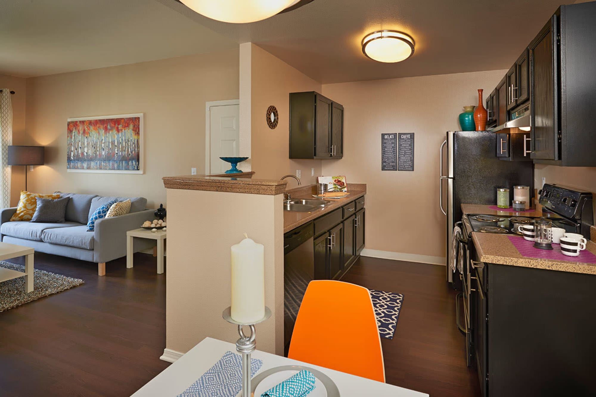Kitchen and living room at Crossroads at City Center Apartments in Aurora, Colorado