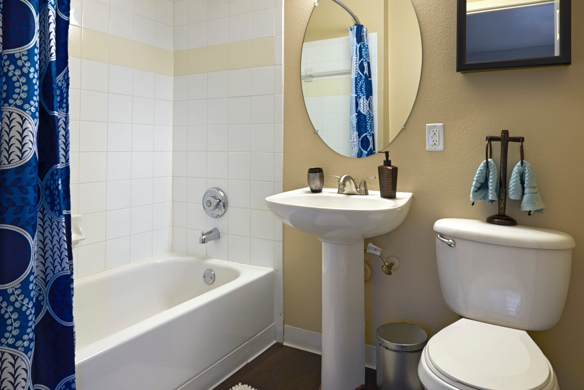 Bathroom with pedestal sink and tub at Crossroads at City Center Apartments in Aurora, Colorado