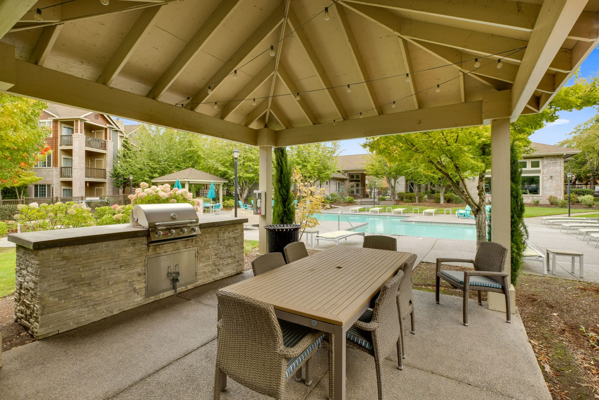A covered patio area by the pool with a large wooden table and rope lights on the ceiling at The Grove at Orenco Station in Hillsboro, Oregon