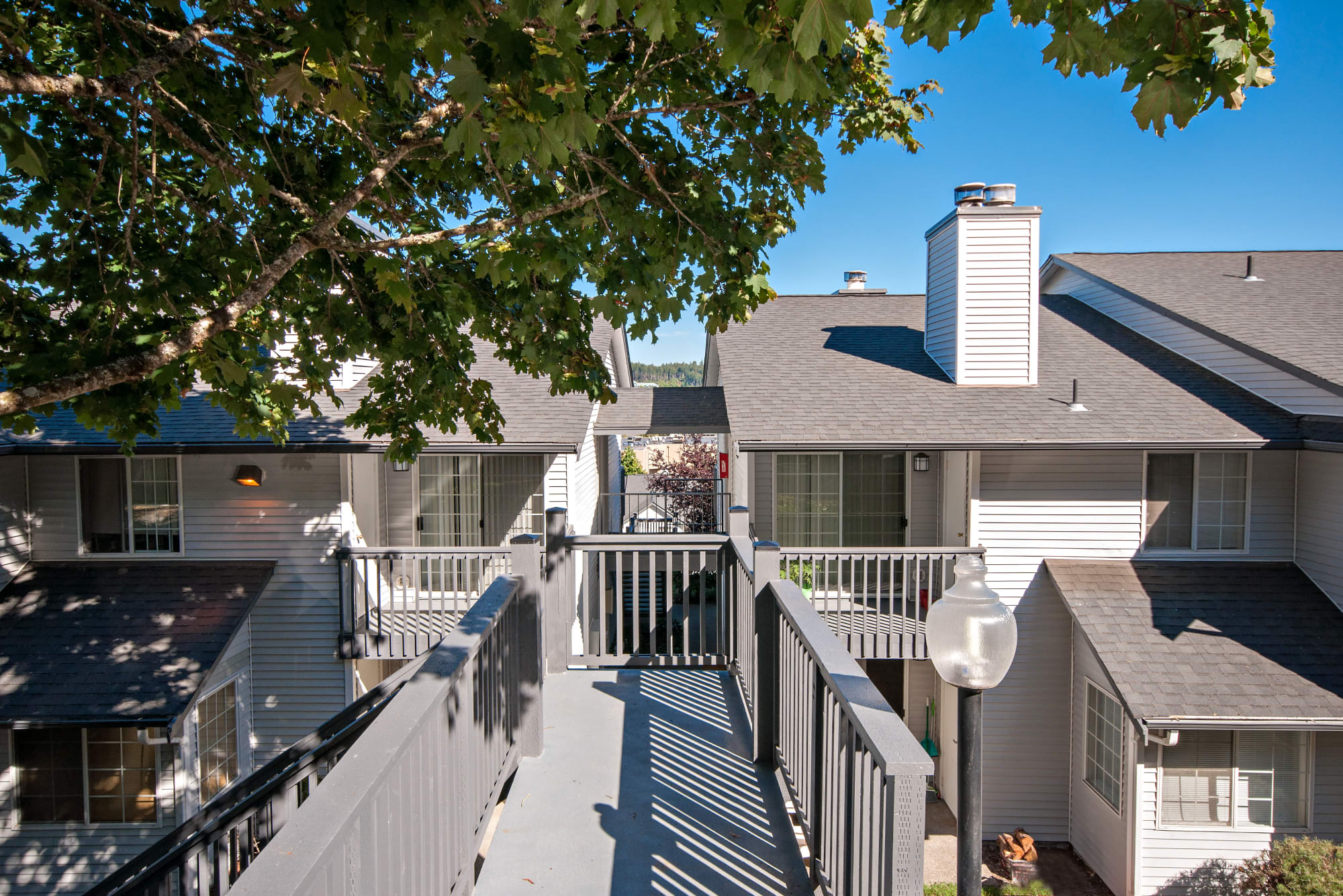 A sunny balcony walkway between apartments at Wellington Apartment Homes in Silverdale, Washington