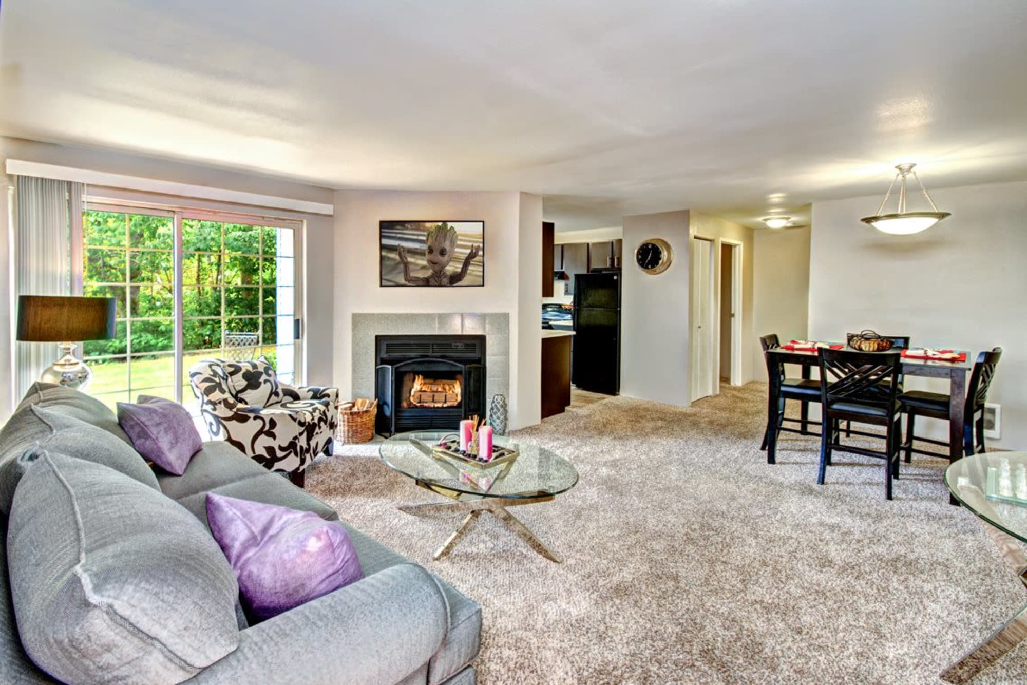 A spacious living room and dining room complete with a fireplace at Wellington Apartment Homes in Silverdale, Washington