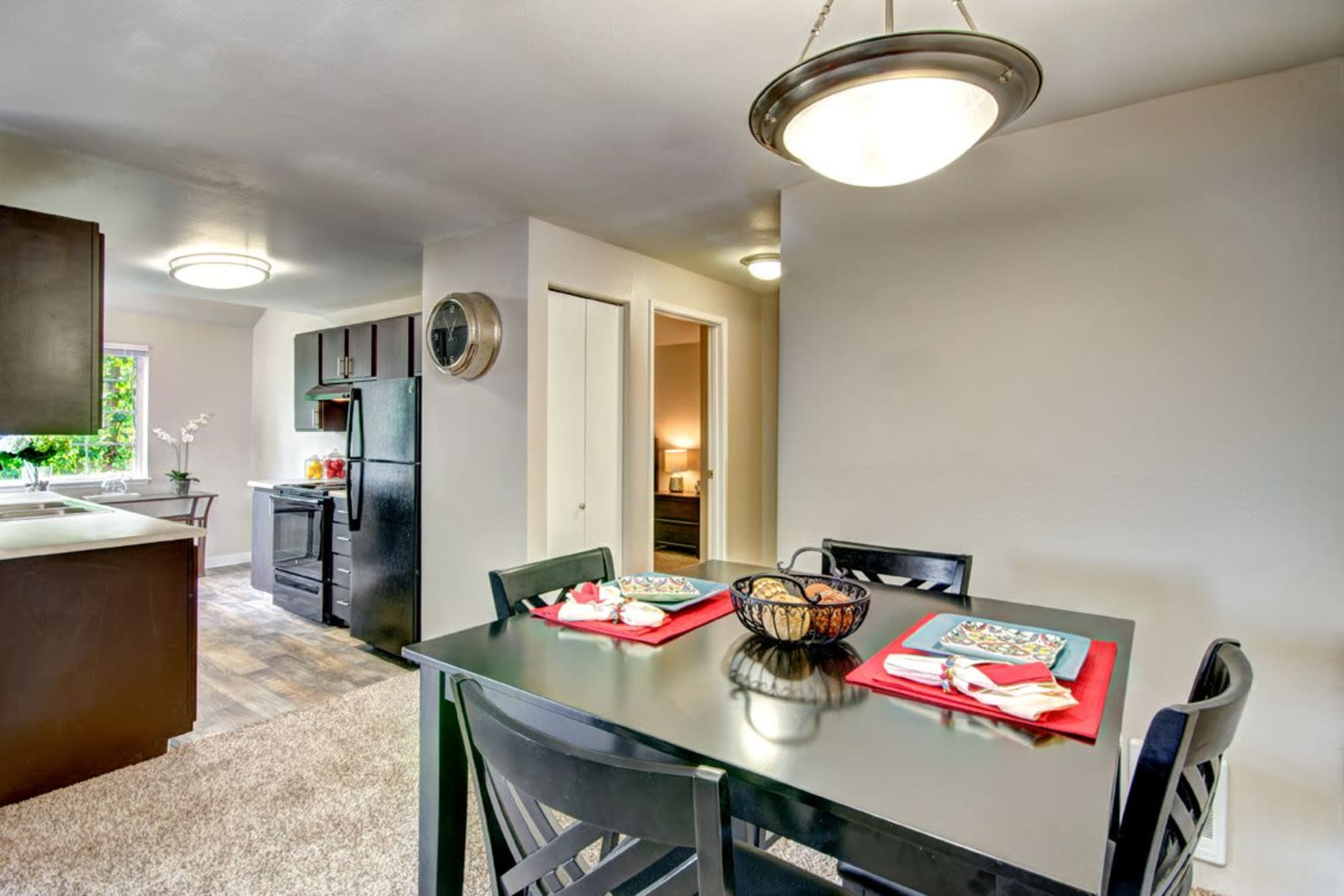 The dining room adjacent to the kitchen in an apartment at Wellington Apartment Homes in Silverdale, Washington