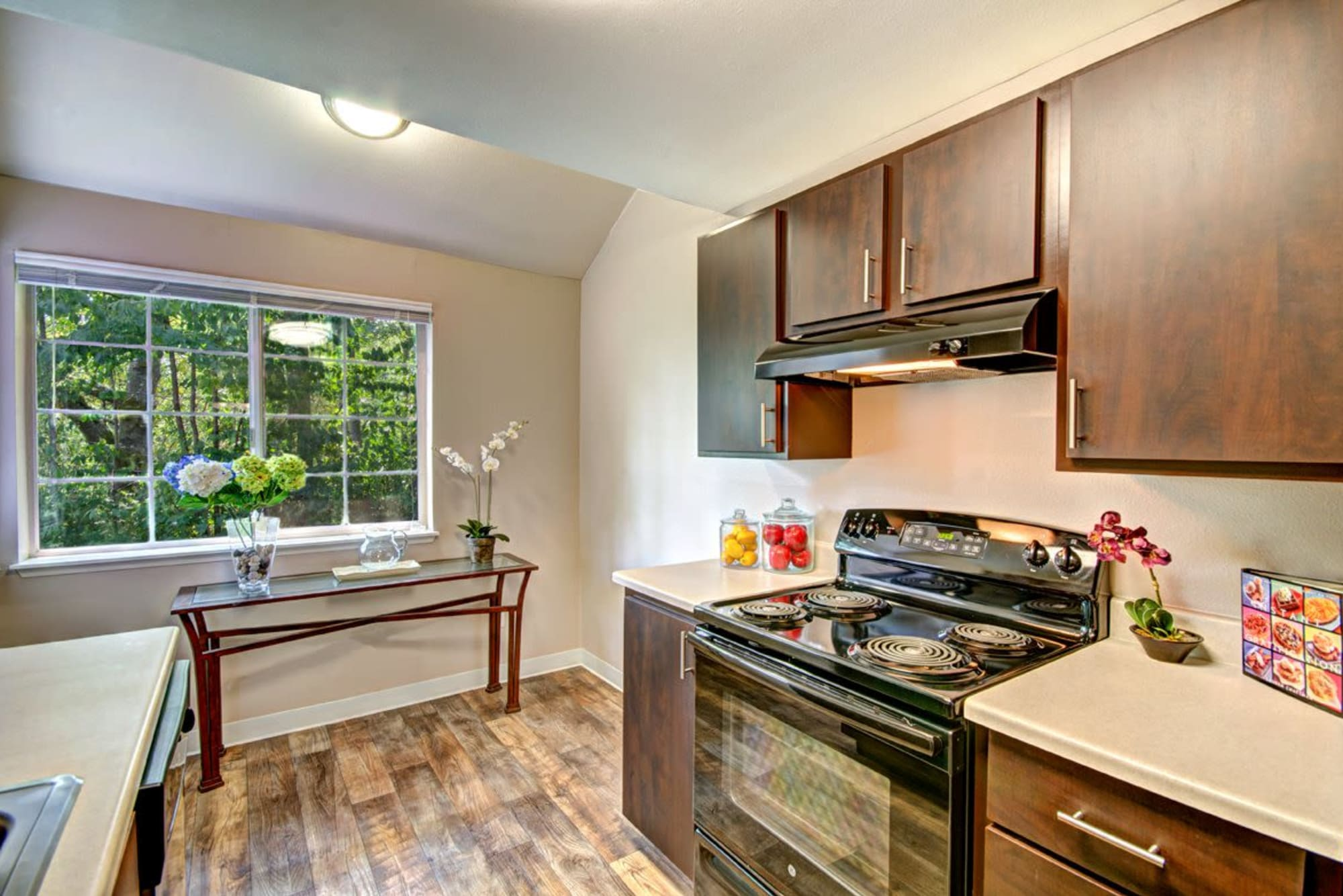 A spacious kitchen with hardwood-style flooring at Wellington Apartment Homes in Silverdale, Washington