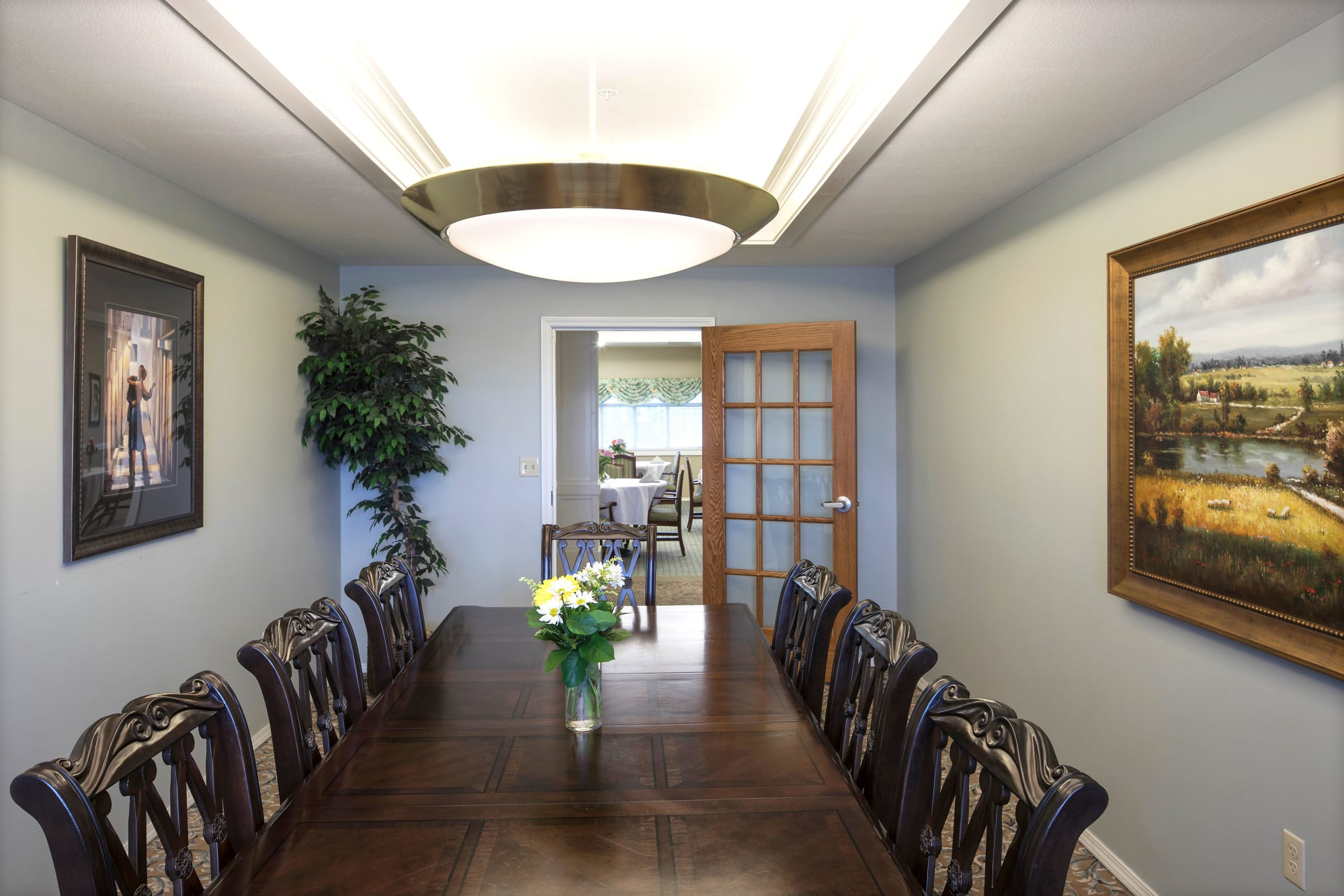Private dining room with a dark wood table at Canoe Brook Assisted Living & Memory Care in Catoosa, Oklahoma